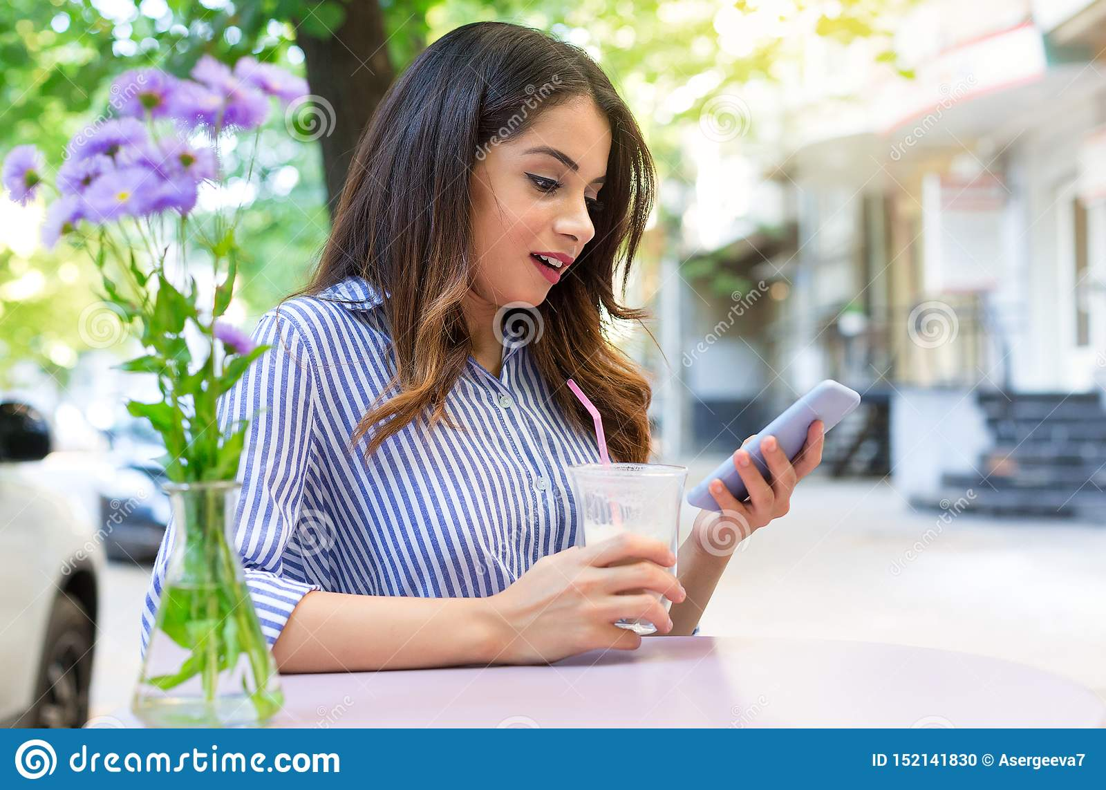 Förvånad ung kvinna som dricker kaffe i ett kafé och ser telefonen Kopieringsutrymme som ?r utomhus-