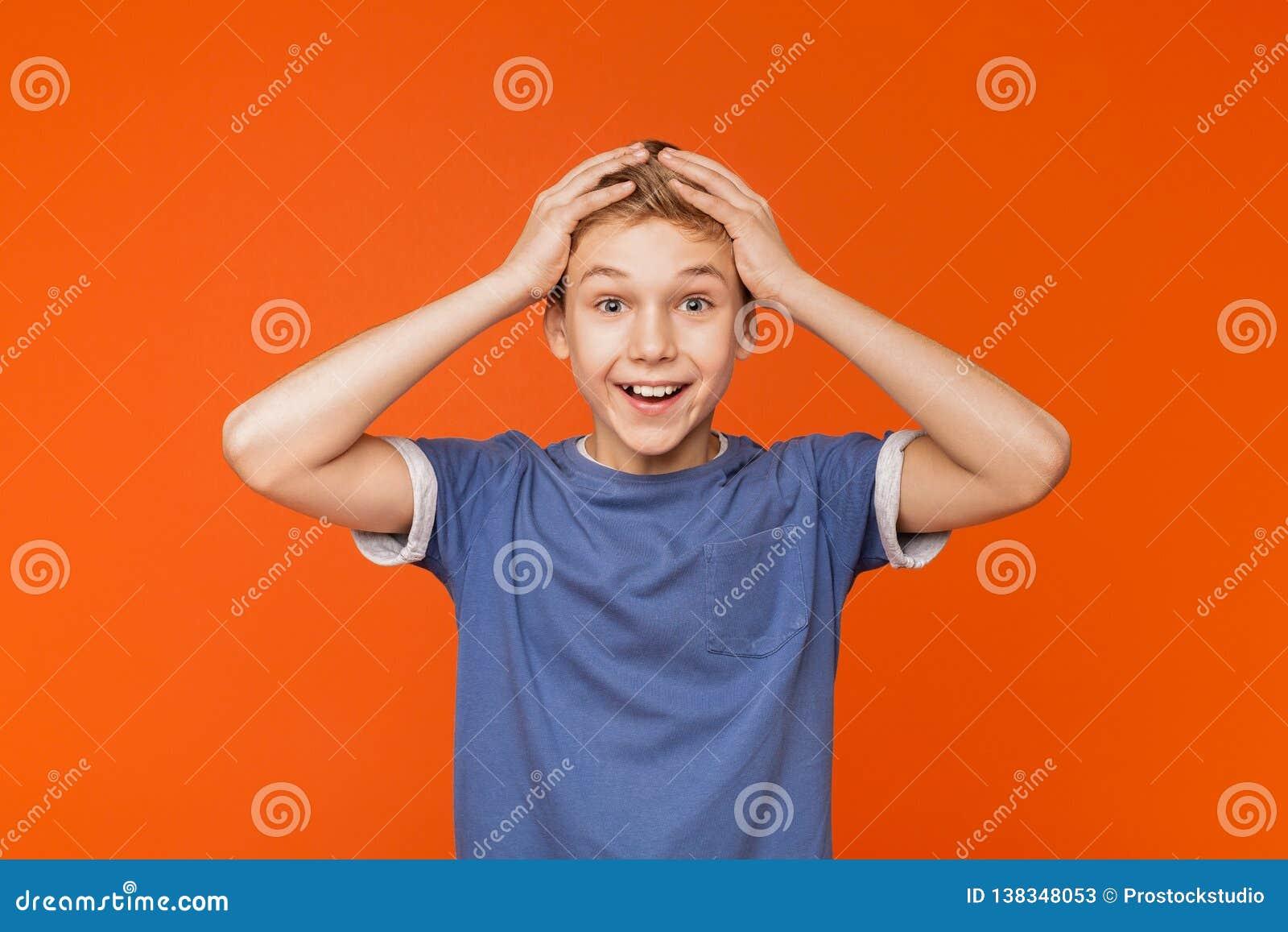 Förvånad upphetsad pys som rymmer händer på huvudet