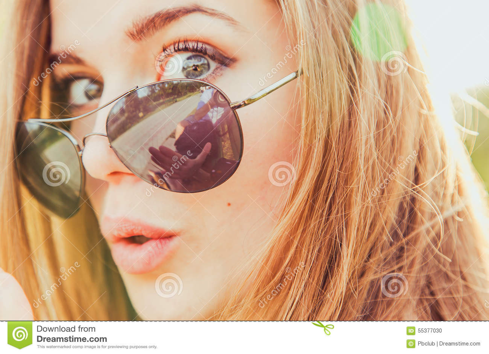 Förvånade unga Woamn i solglasögon