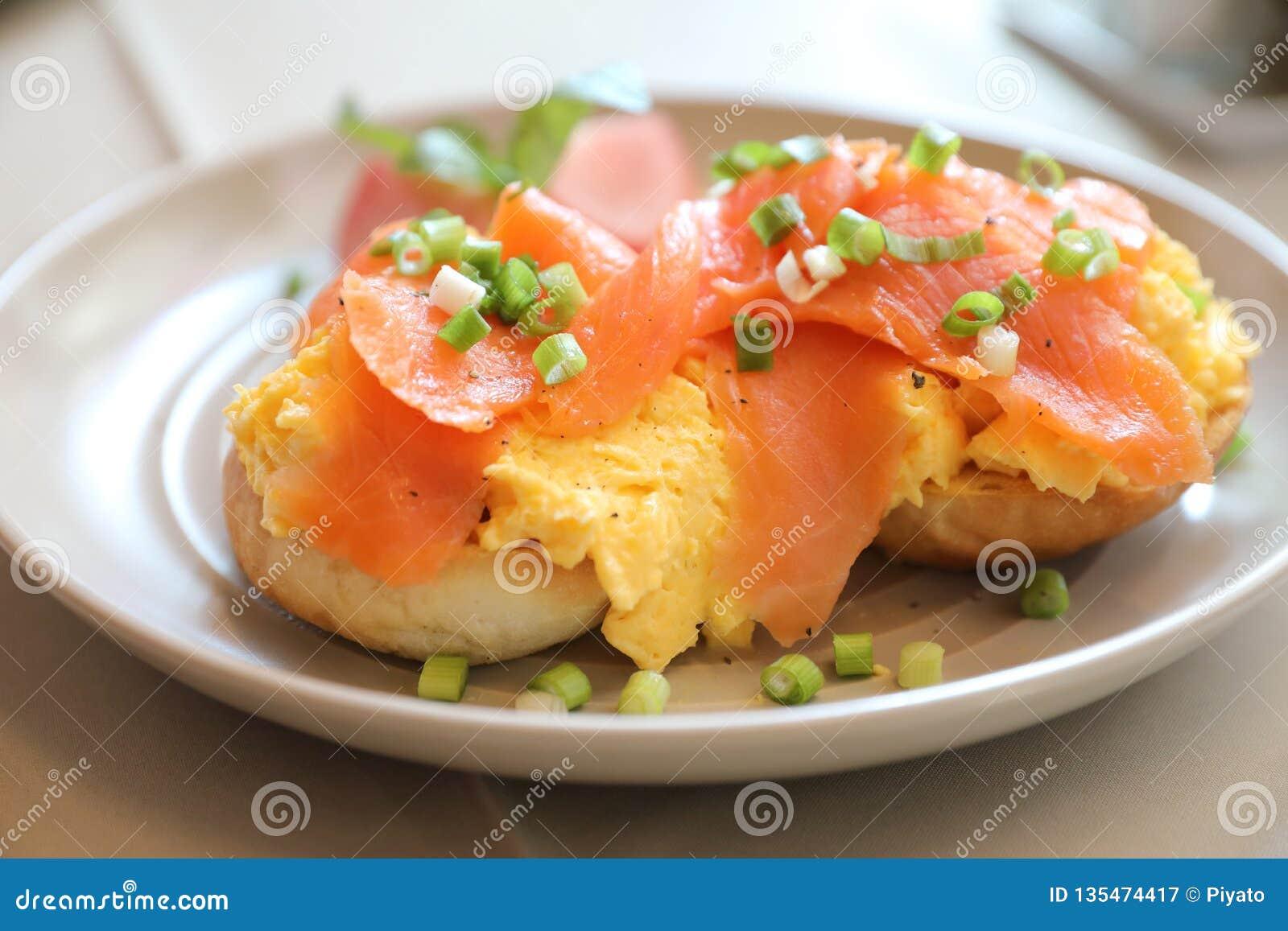 Förvanskade ägg med den rökte laxen på rostat bröd, frukostmat