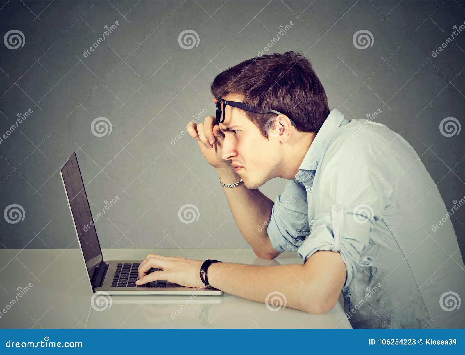 Förvirrad man med bärbara datorn på grå färger