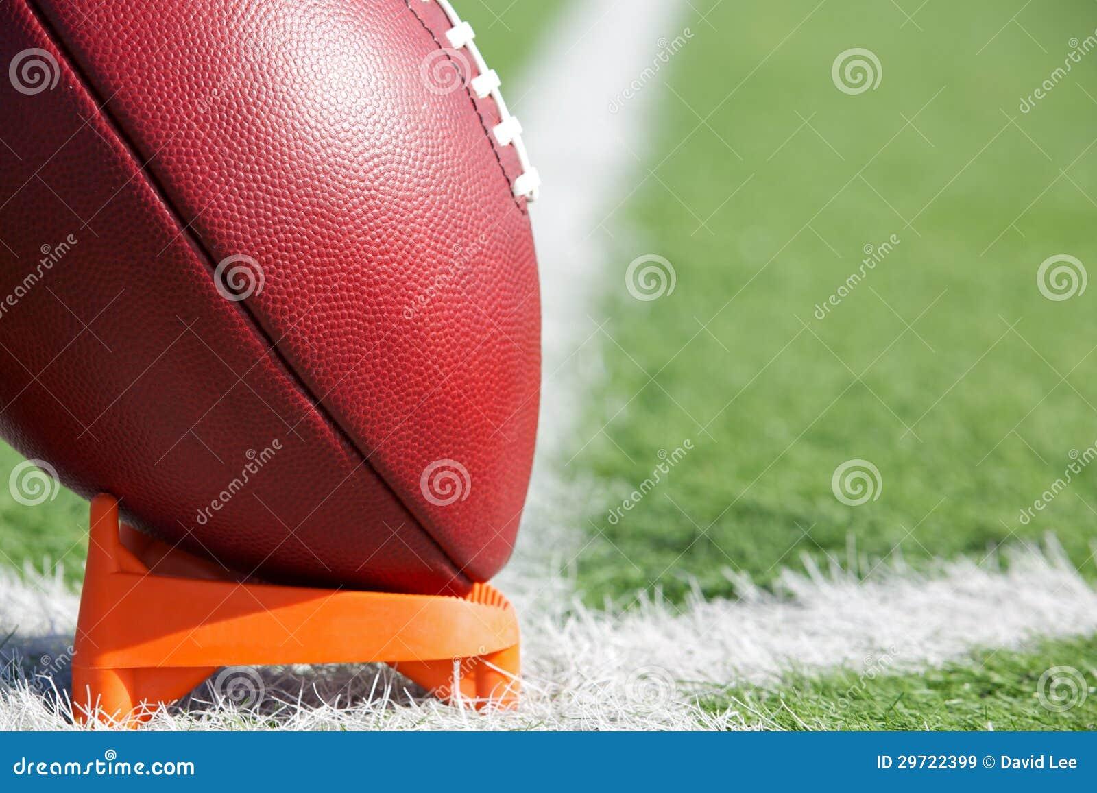 Fútbol americano juntado con te para arriba para el saque de centro