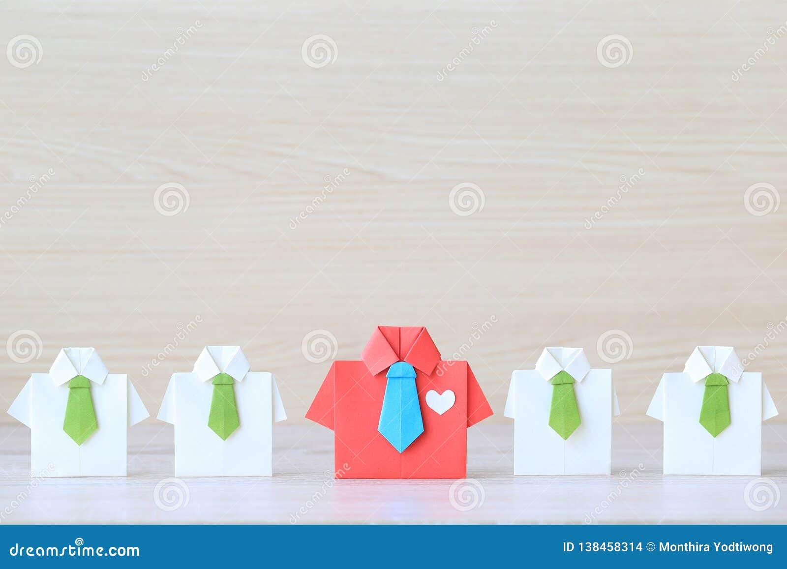 Führung und Teamwork-Konzept, rotes Hemd des Origamis mit Bindung und Führung unter kleinem gelbem Hemd auf wooder Hintergrund