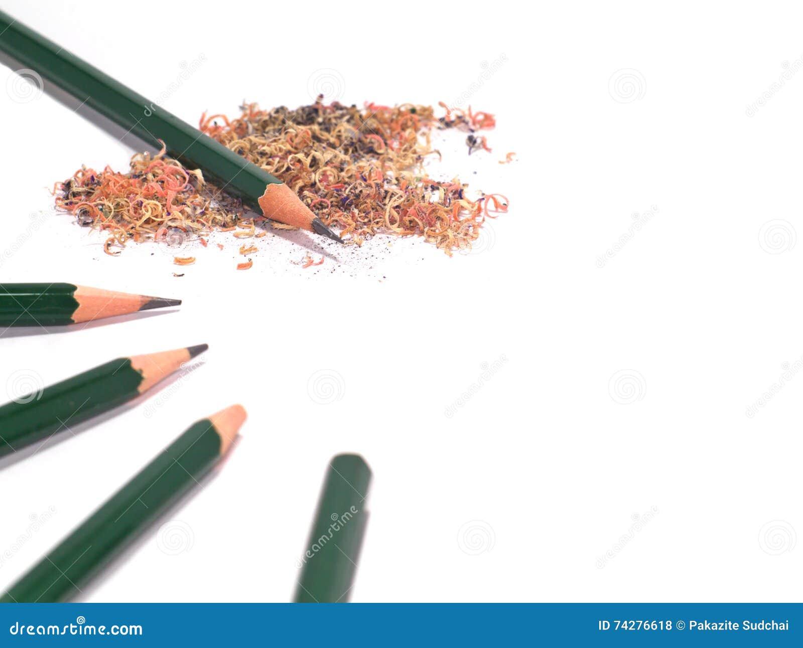 Fünf geschärft und unsharpened grüne Bleistifte mit Bleistiftsägemehl