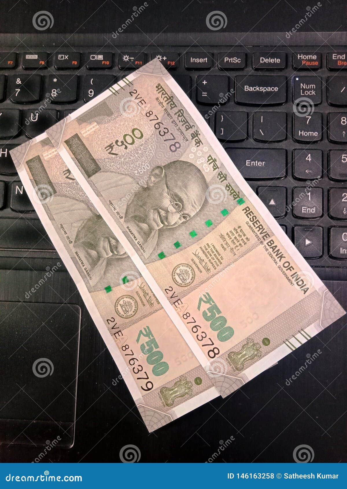 Fünfhundert Rupien indische Banknoten über eine Laptoptastatur