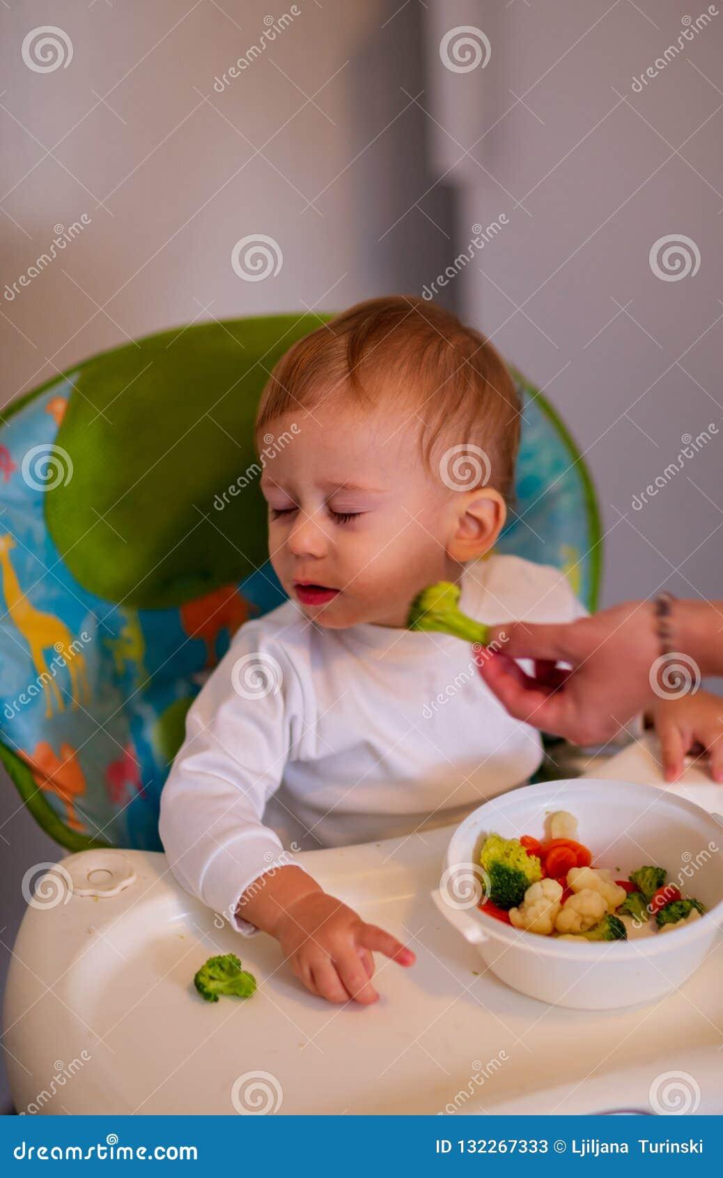 Fütterungsbaby mit Gemüse - schönes Baby lehnt ab, broc zu essen
