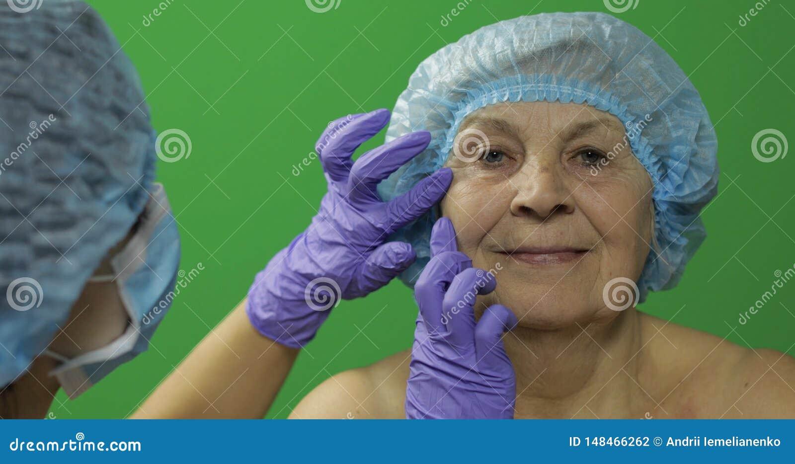 F?mea idosa de sorriso no chap?u protetor Cirurgi?o pl?stico que verifica a cara da mulher
