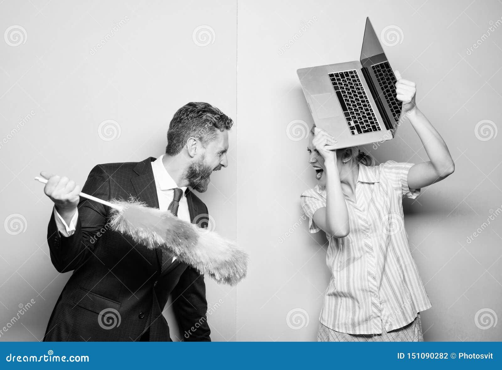 F? p? en kamp Makest?llning med dammborsten medan fruinnehavb?rbar dator Par av den stiliga mannen och den n?tta kvinnan