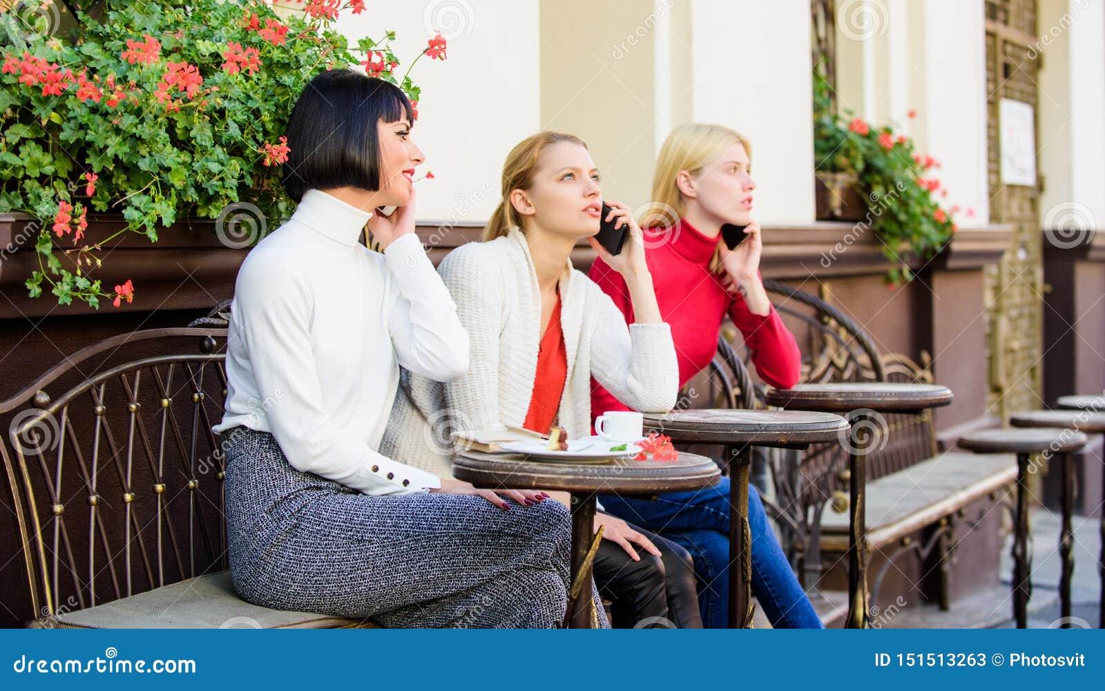 F?r Digital f?r m?ngfaldfolkanslutning bl?ddra apparater Social nätverkande på kafét tre flickor i kafét som talar på telefonen