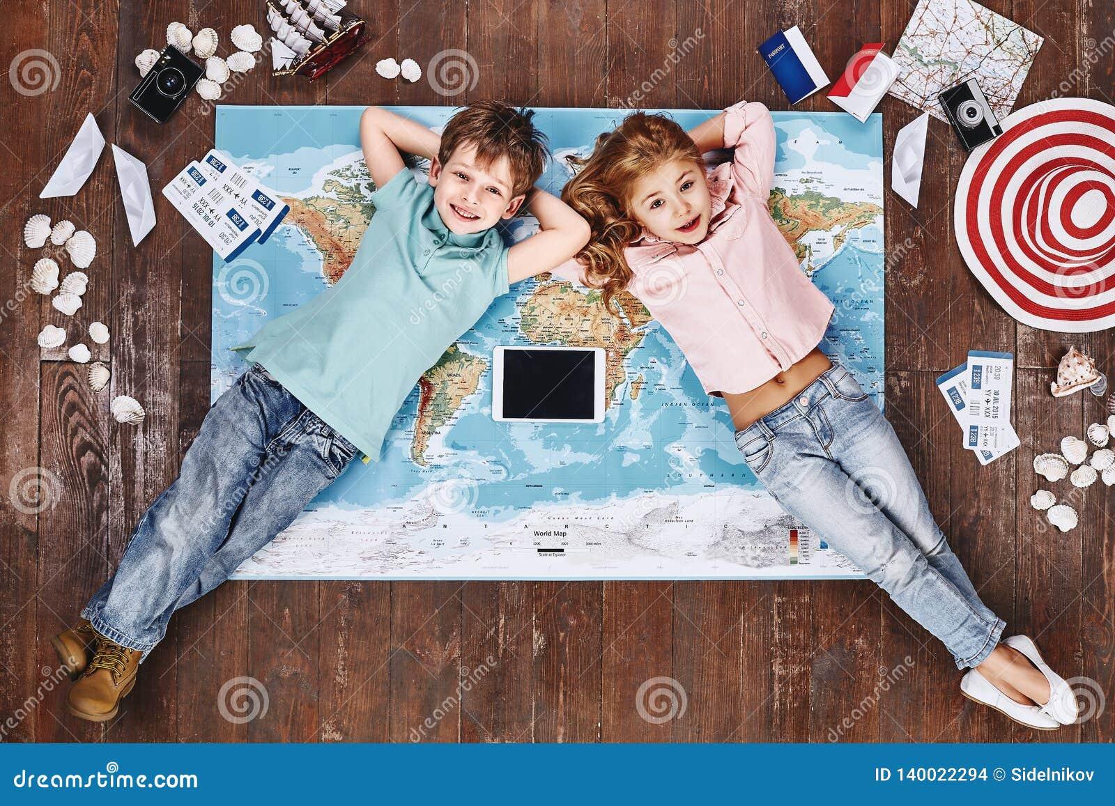 F r Mim e n d S Crianças que encontram-se no mapa do mundo perto dos artigos e do iPad do curso