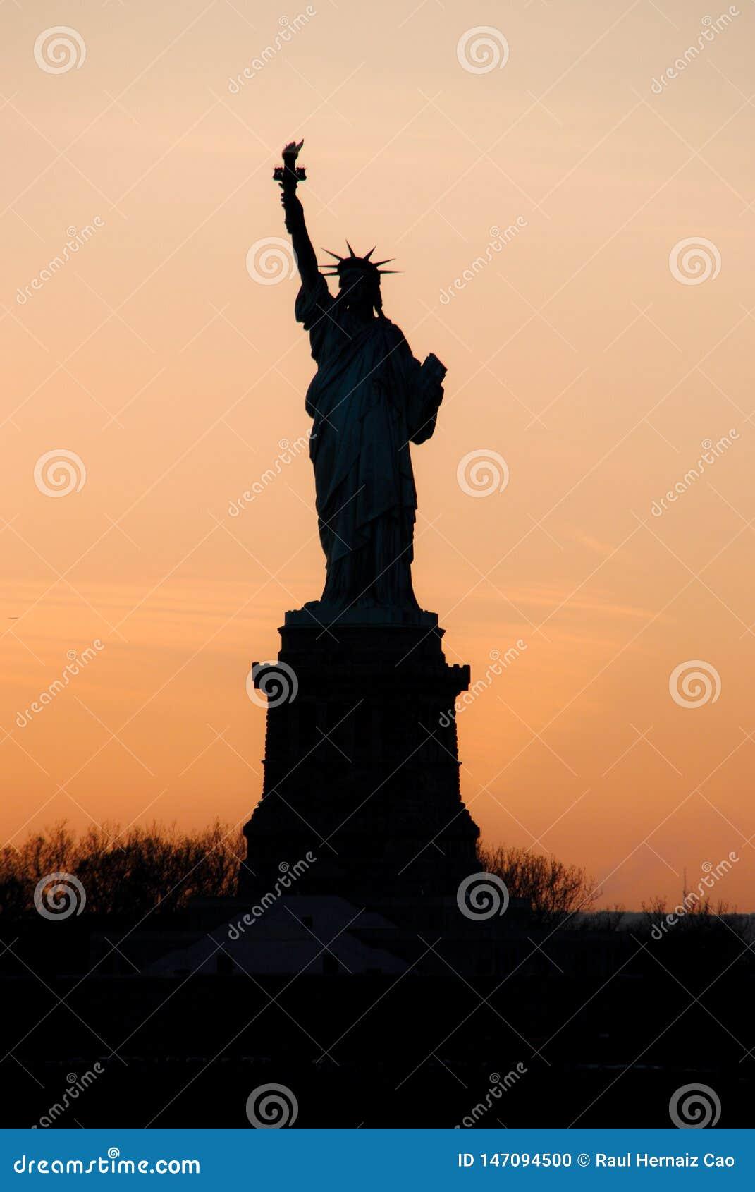F?rbluffa sikten av statyn av frihet, p? solnedg?ngen New York symbol