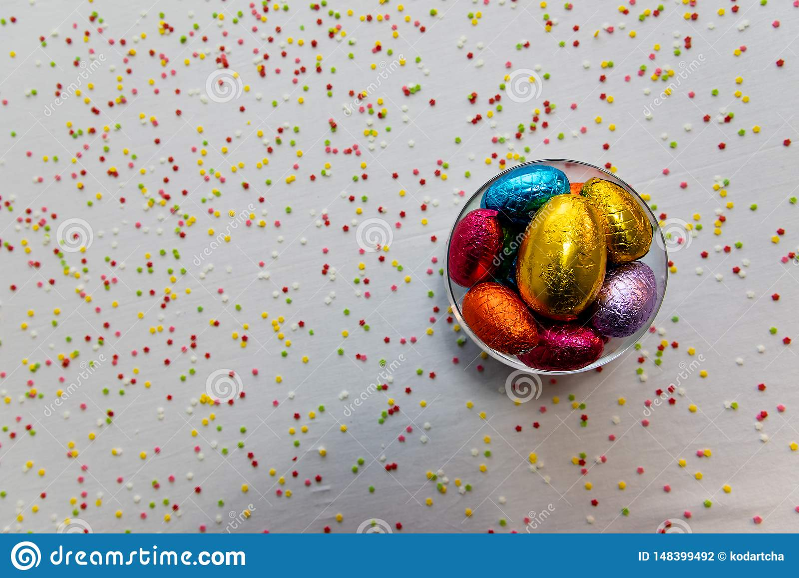 F?rgrika chokladeaster ?gg i en genomskinlig bunke med vit bakgrund och suddiga konfettier