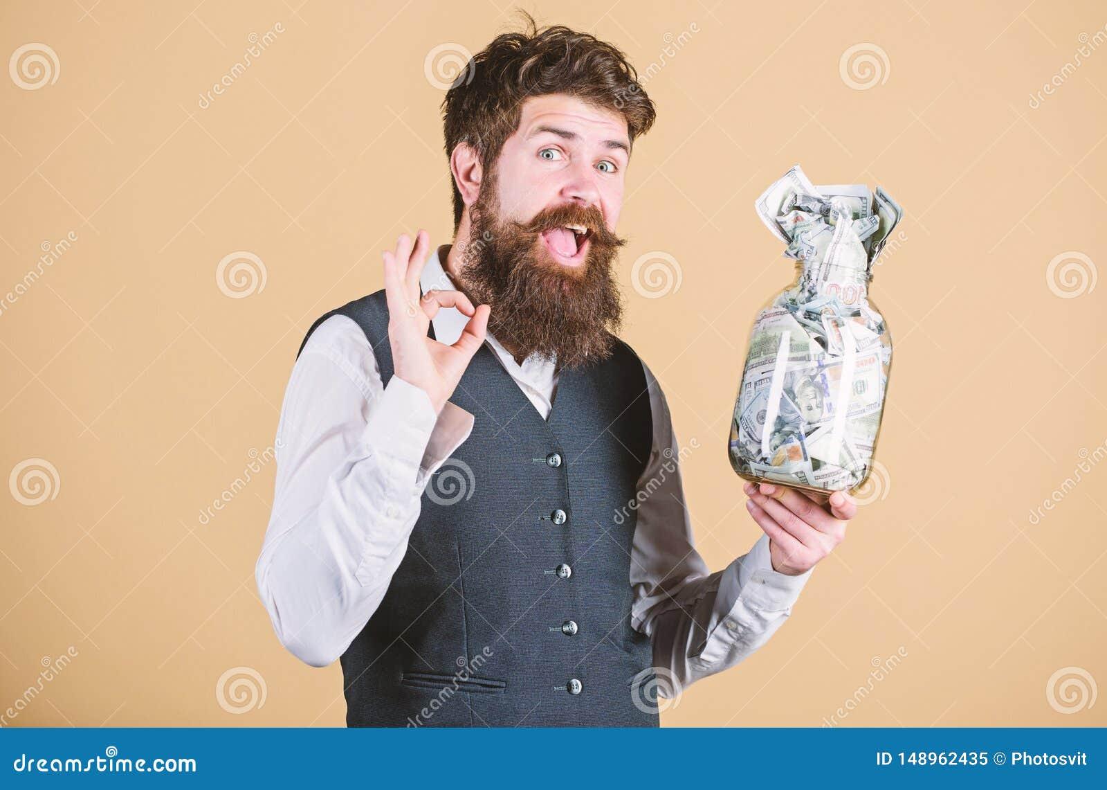 F? rikt Rikt g?ra en gest f?r aff?rsman som ?r ok med pengar i exponeringsglaskrus Sk?ggig rikeman med pengarkassa N?r blivet a