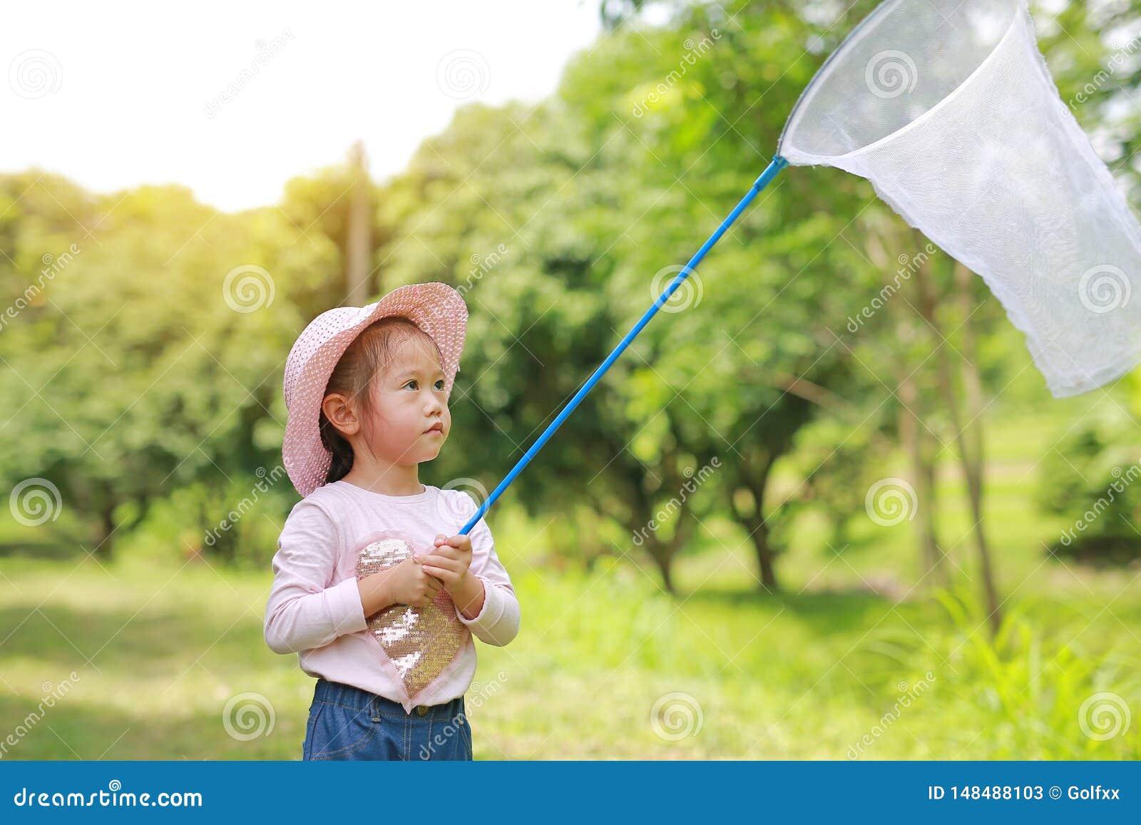 F?rtjusande liten asiatisk hatt f?r flickakl?dersugr?r i ett f?lt med krypet som ?r netto i sommar utomhus- aktivitet