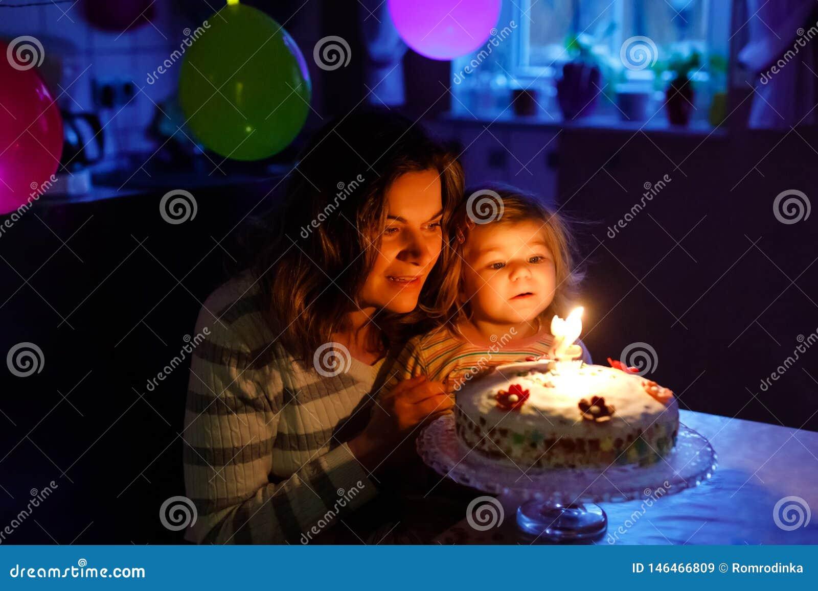 F?rtjusande liten litet barnflicka som firar den andra f?delsedagen Behandla som ett barn barndottern och den unga modern som bl?