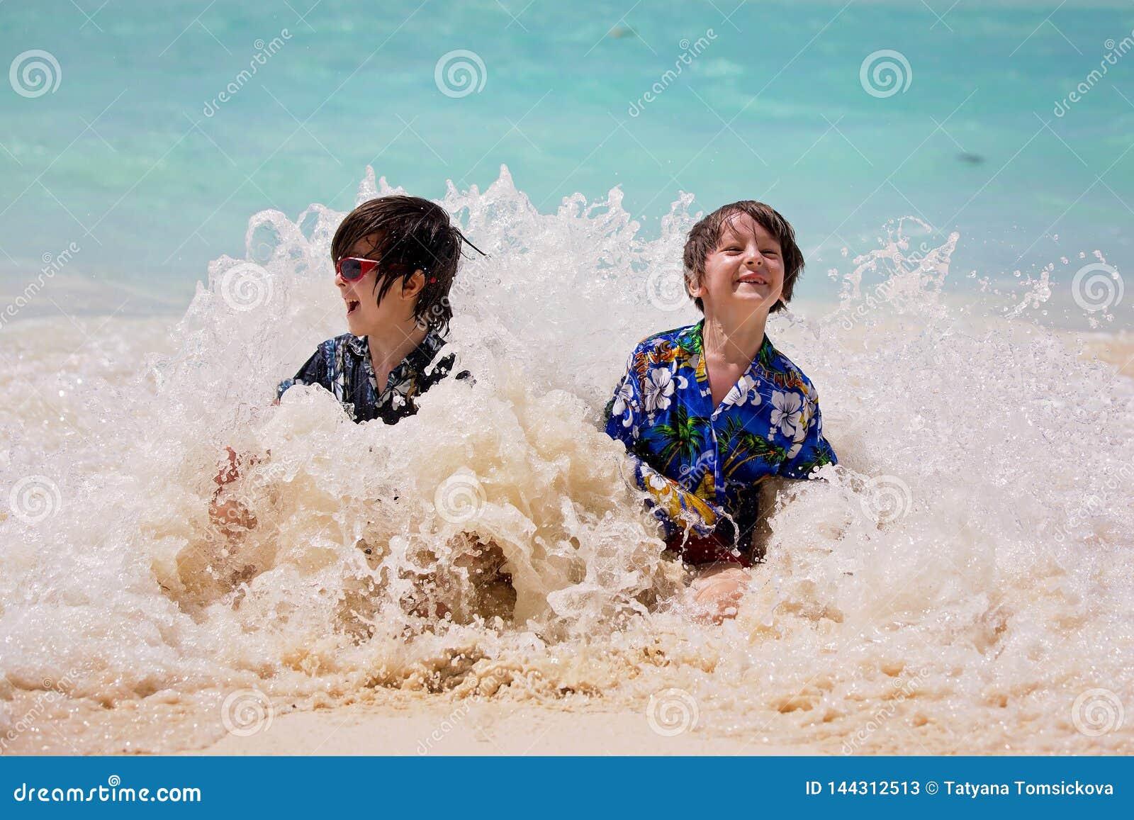 F?rtjusande f?rskole- barn, pojkar och att ha gyckel p? havstranden Upphetsade barn som spelar med v?gor, simning som lyckligt pl