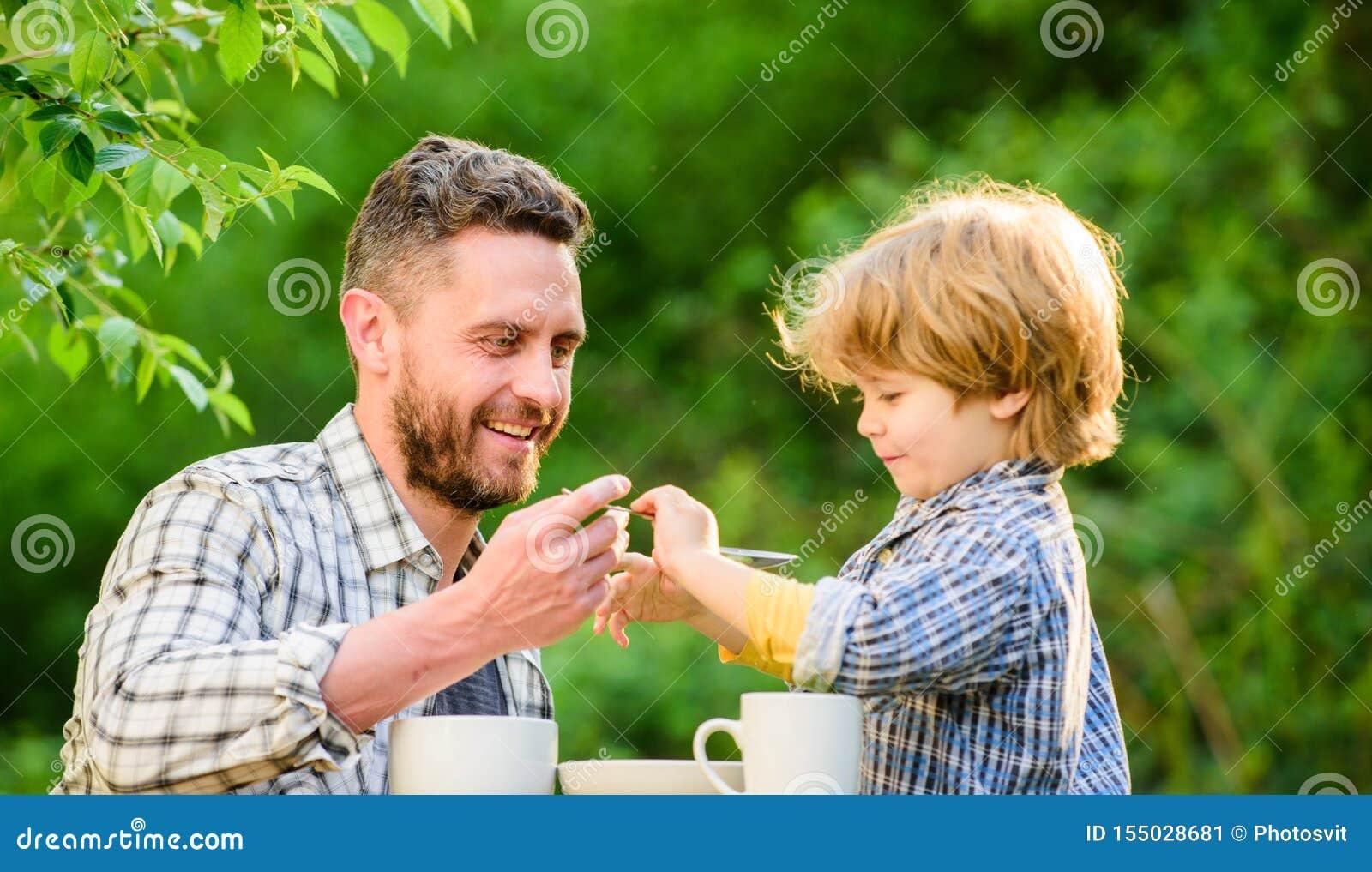 F?tterungssohn nat?rliche Nahrungsmittel Stadium der Entwicklung Zufuhrsohnkörper Vati und Junge drau?en essen und sich einziehen