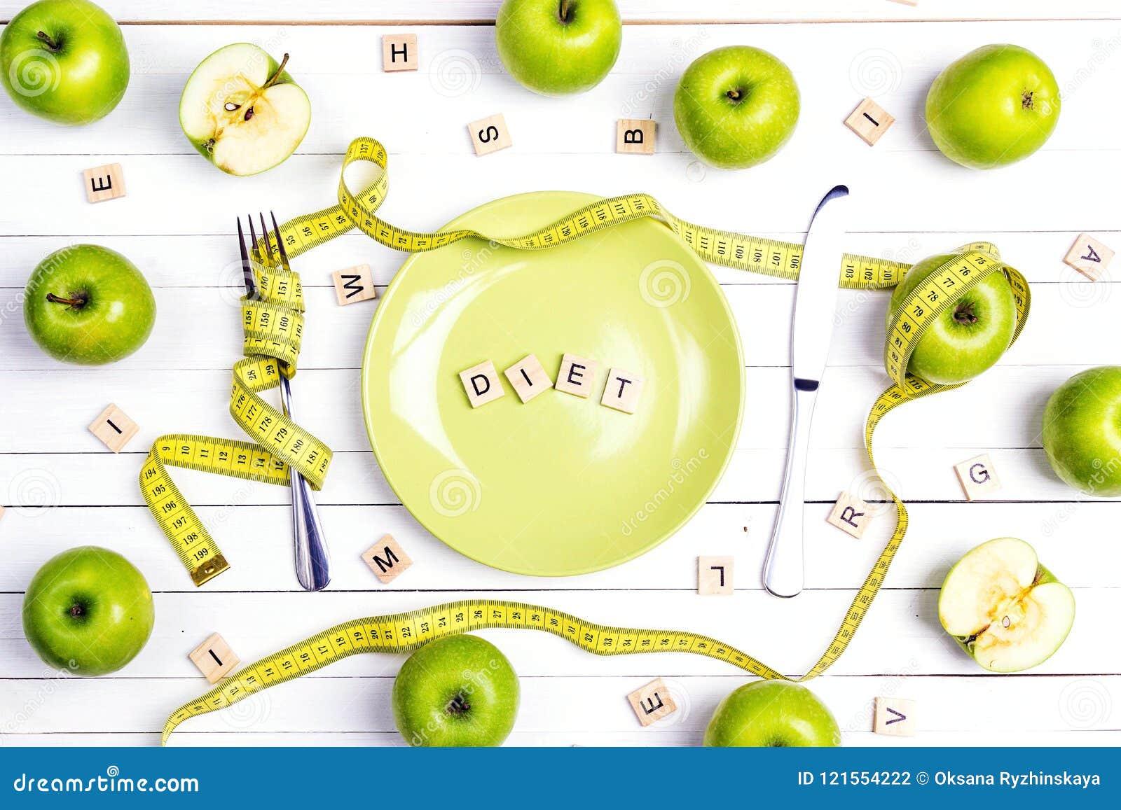 Faça dieta o ajuste da tabela do conceito com cutelaria, a fita de medição amarela e as maçãs verdes na tabela de madeira branca