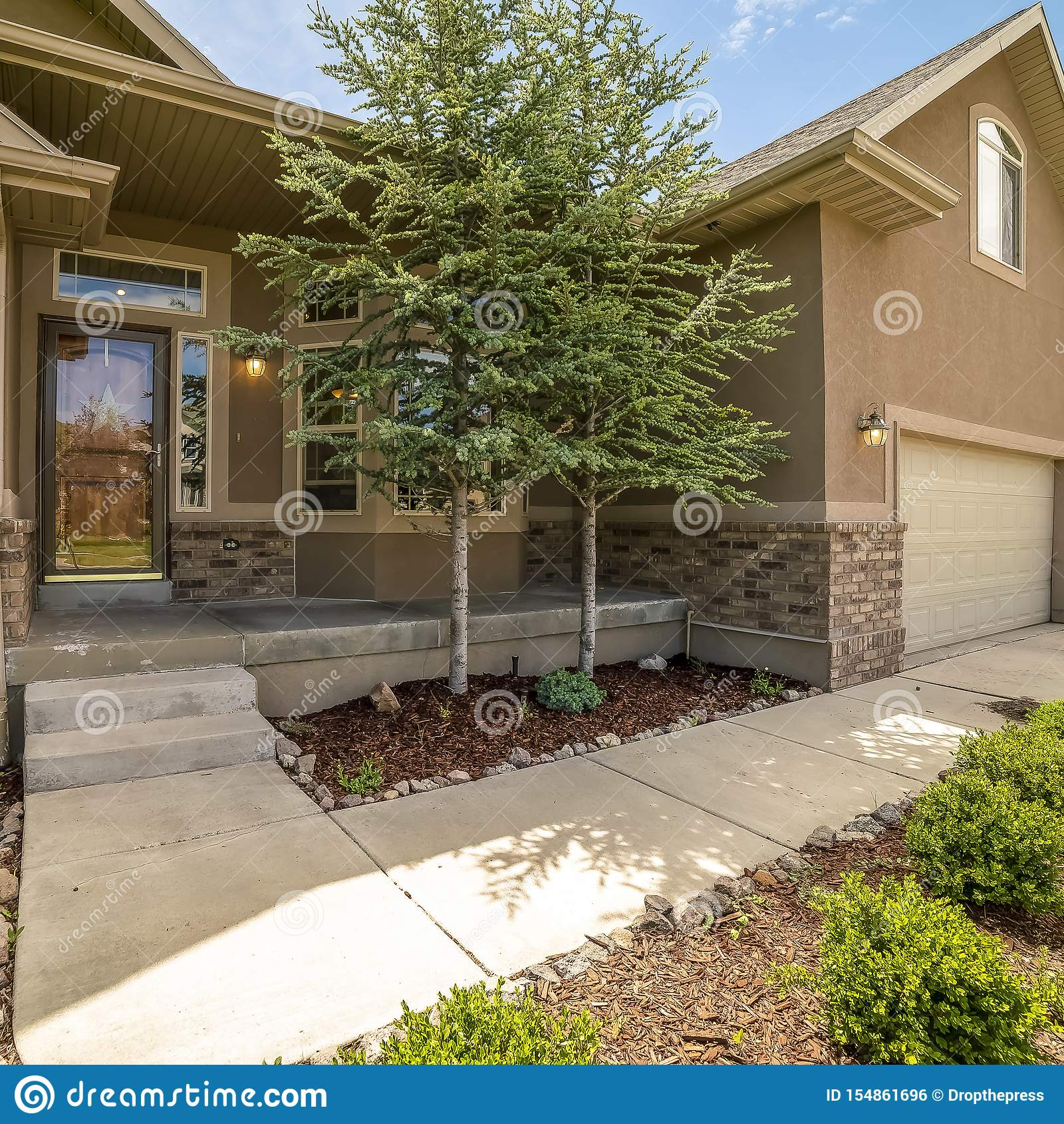 Façade à la maison de place avec la vue du porche et de l entrée principale de porte de garage de yard un jour ensoleillé