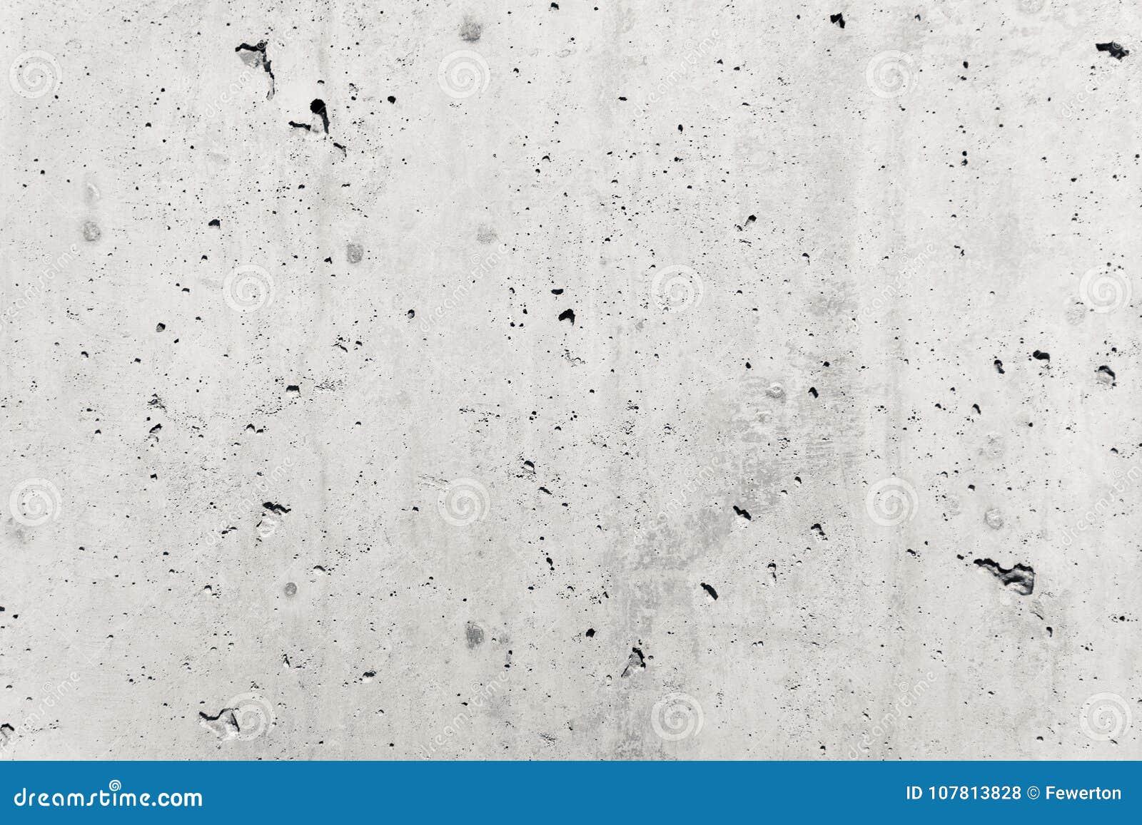 Façade brute grise de mur en béton faite de ciment naturel avec des trous et des imperfections comme fond rustique vide de textur