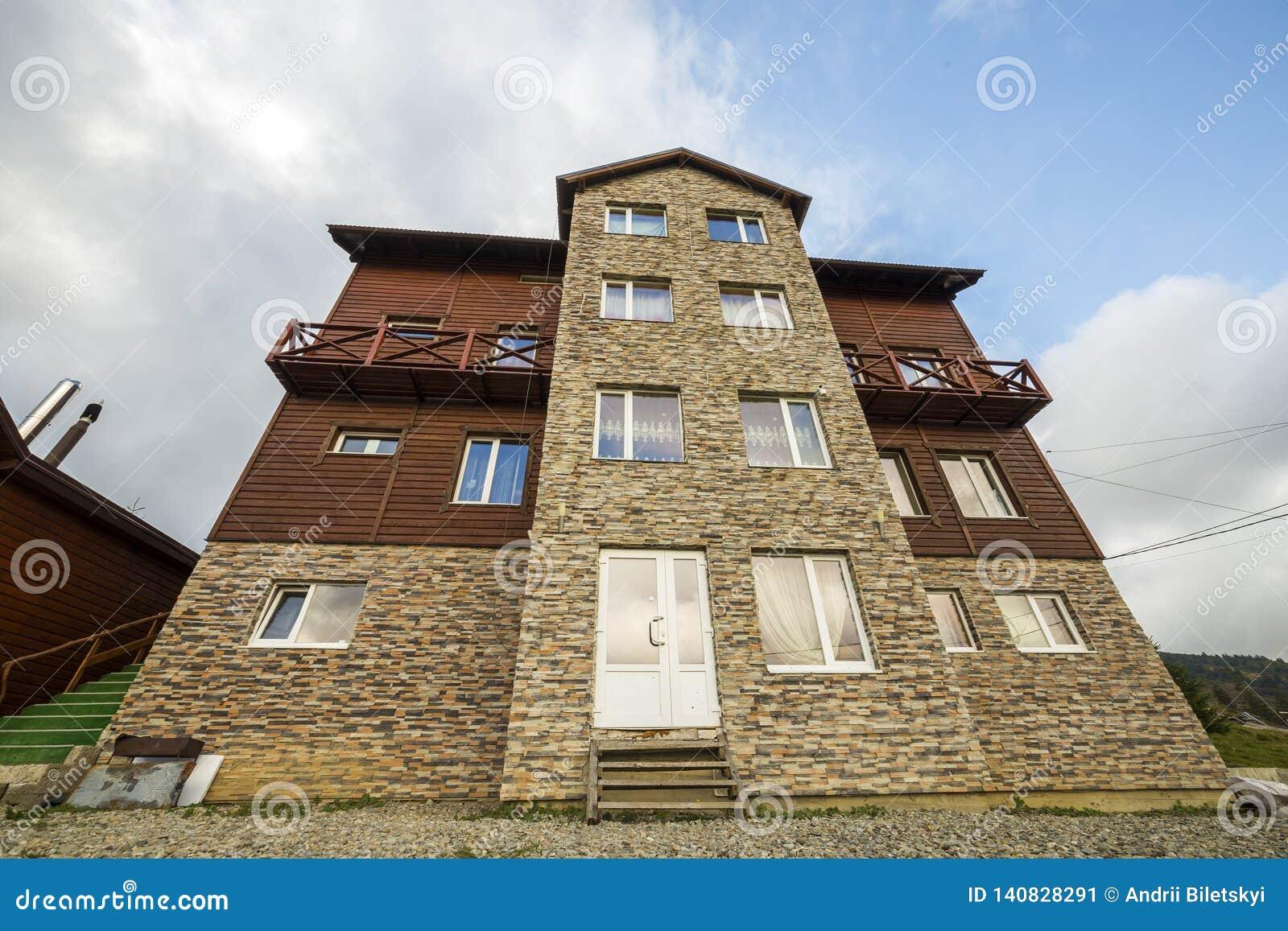 Façade de nouvelle maison en bois de cottage des matériaux et de la pierre de bois de charpente avec le balcon décoratif sur le f