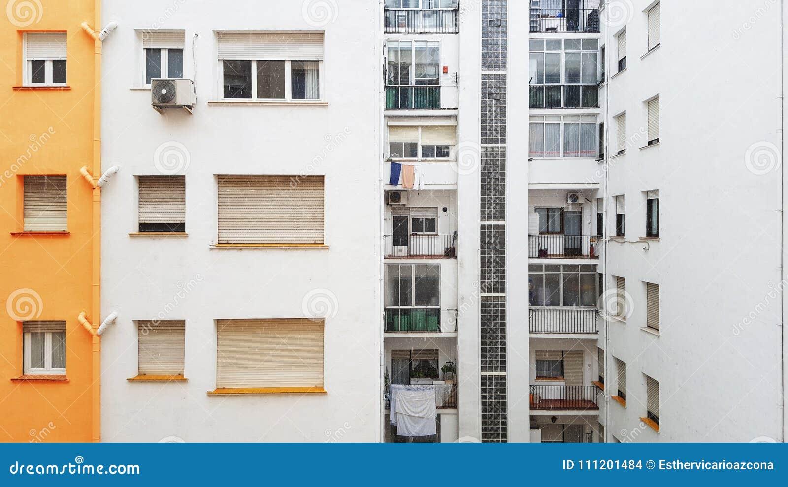 Façade du bâtiment résidentiel tandis que la neige tombe Sur la façade il y a les fenêtres et la climatisation