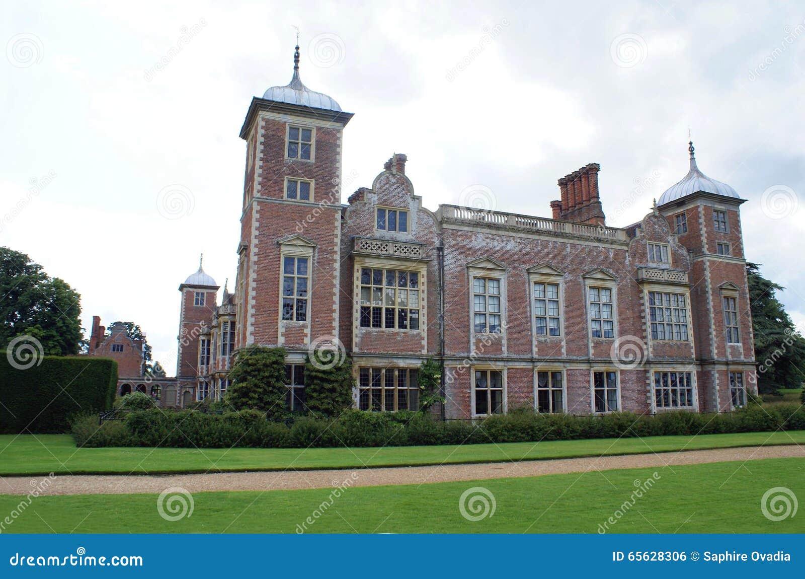 Façade fleurie avec les tours, les fenêtres en saillie, et les cheminées voûtées