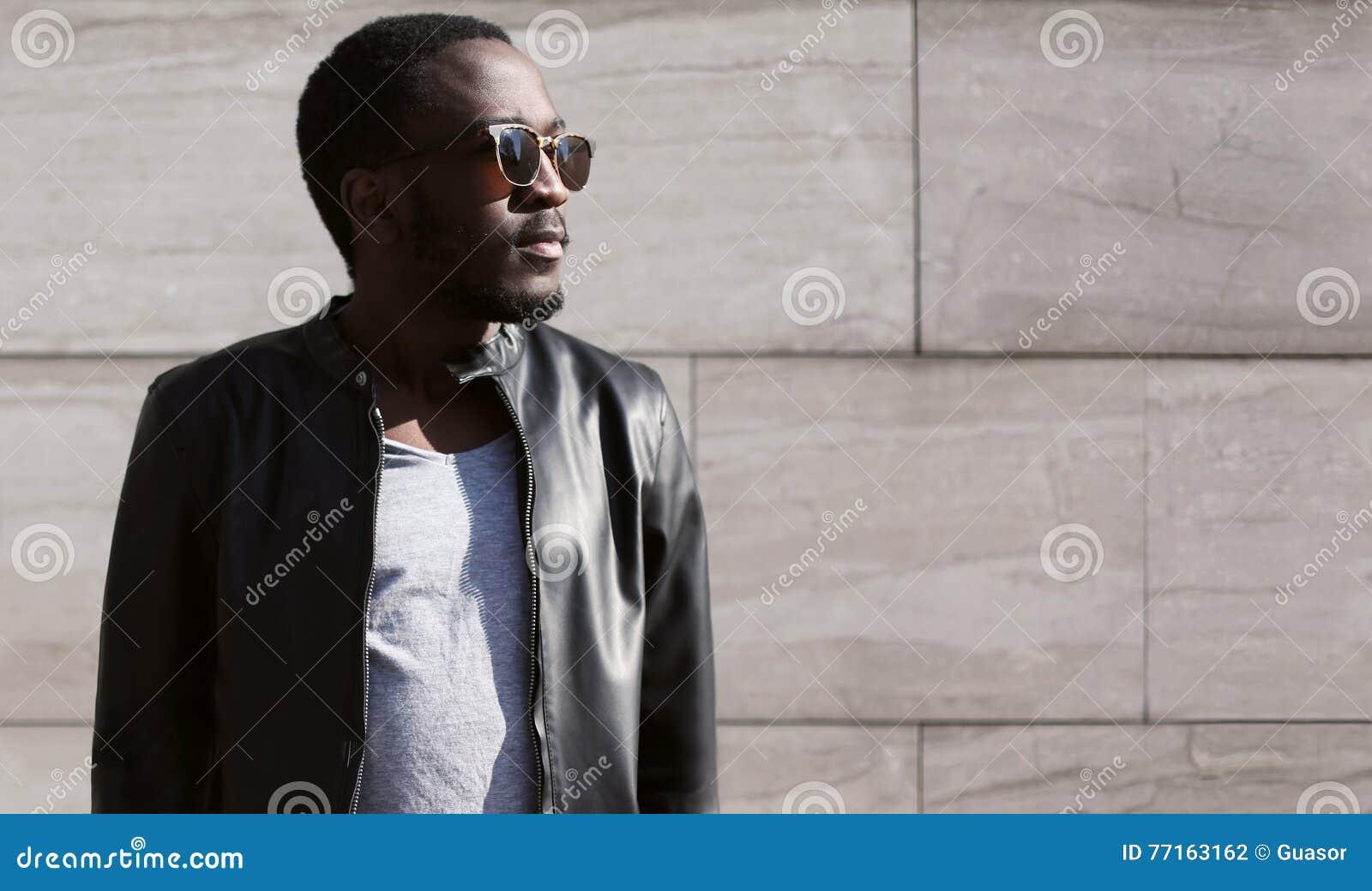 Façonnez à port africain d homme les lunettes de soleil et la roche noire la veste en cuir au-dessus de la soirée texturisée de f