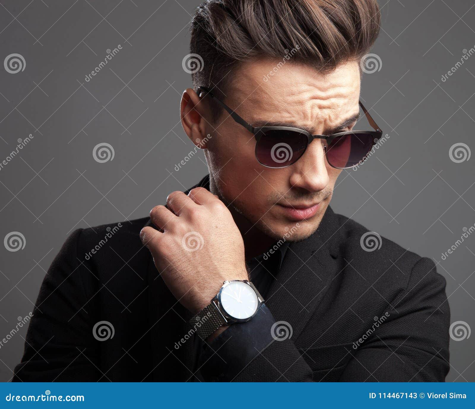 Façonnez l homme montrant sa montre et regardant vers le bas au côté