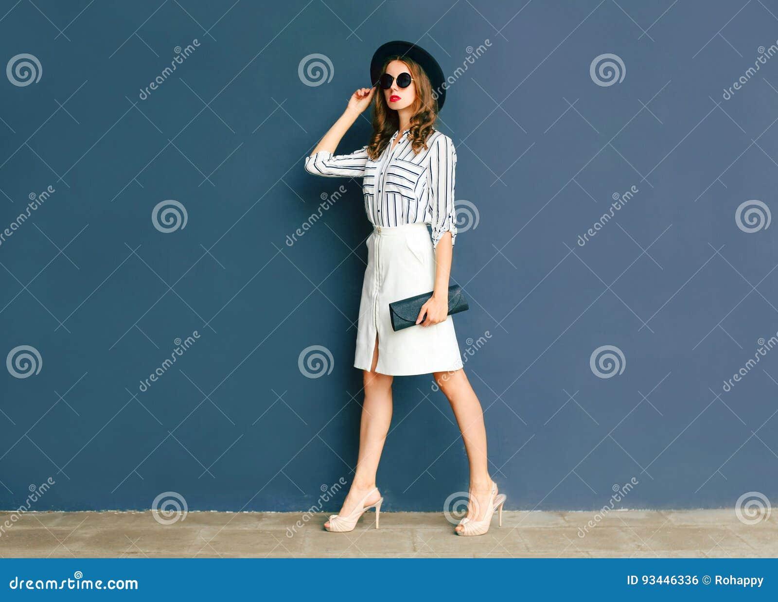Façonnez la femme élégante utilisant un chapeau noir et une jupe de blanc