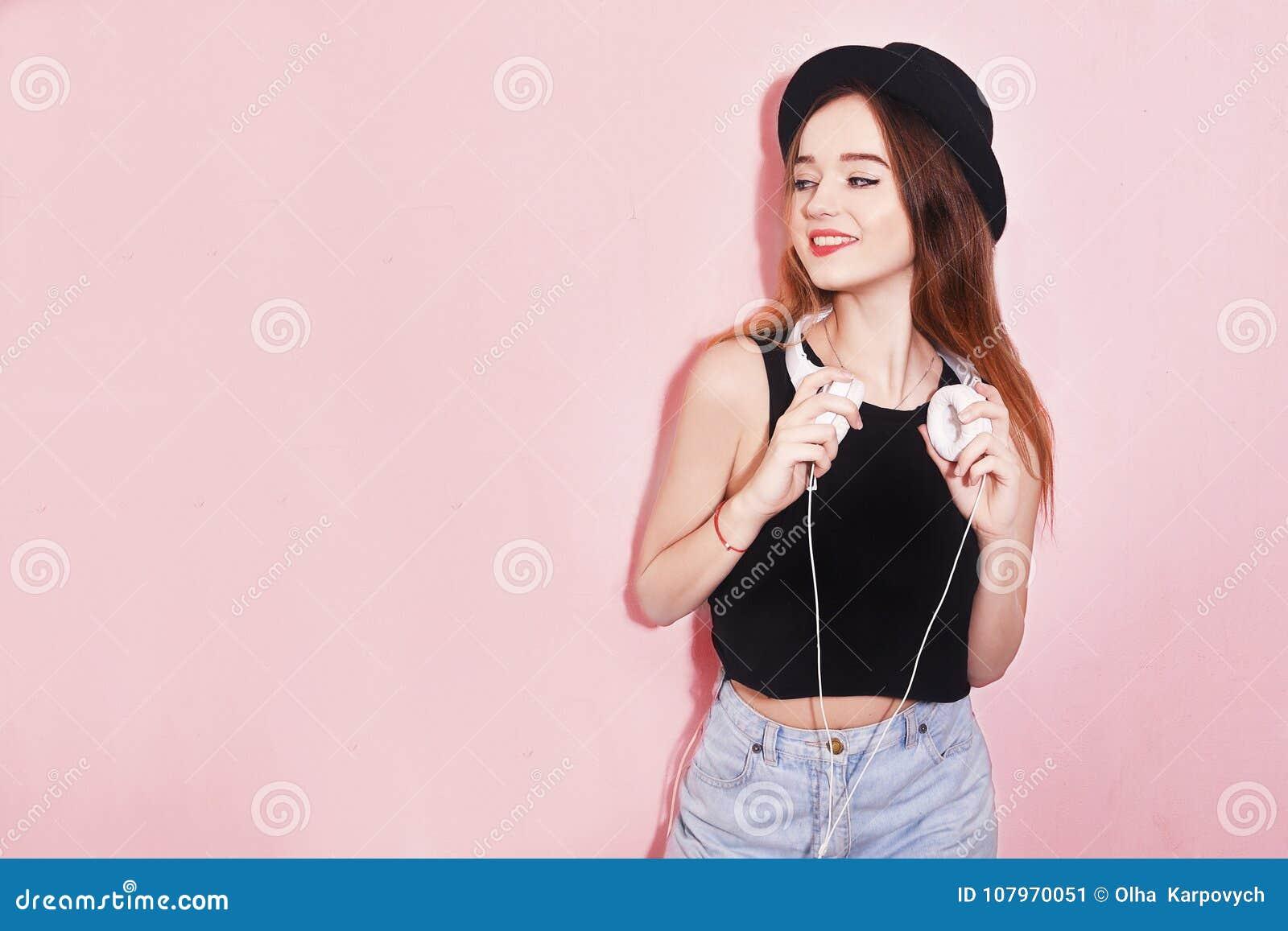 Façonnez la femme assez fraîche dans le chapeau et des écouteurs écoutant la musique au-dessus du fond rose Belle jeune adolescen