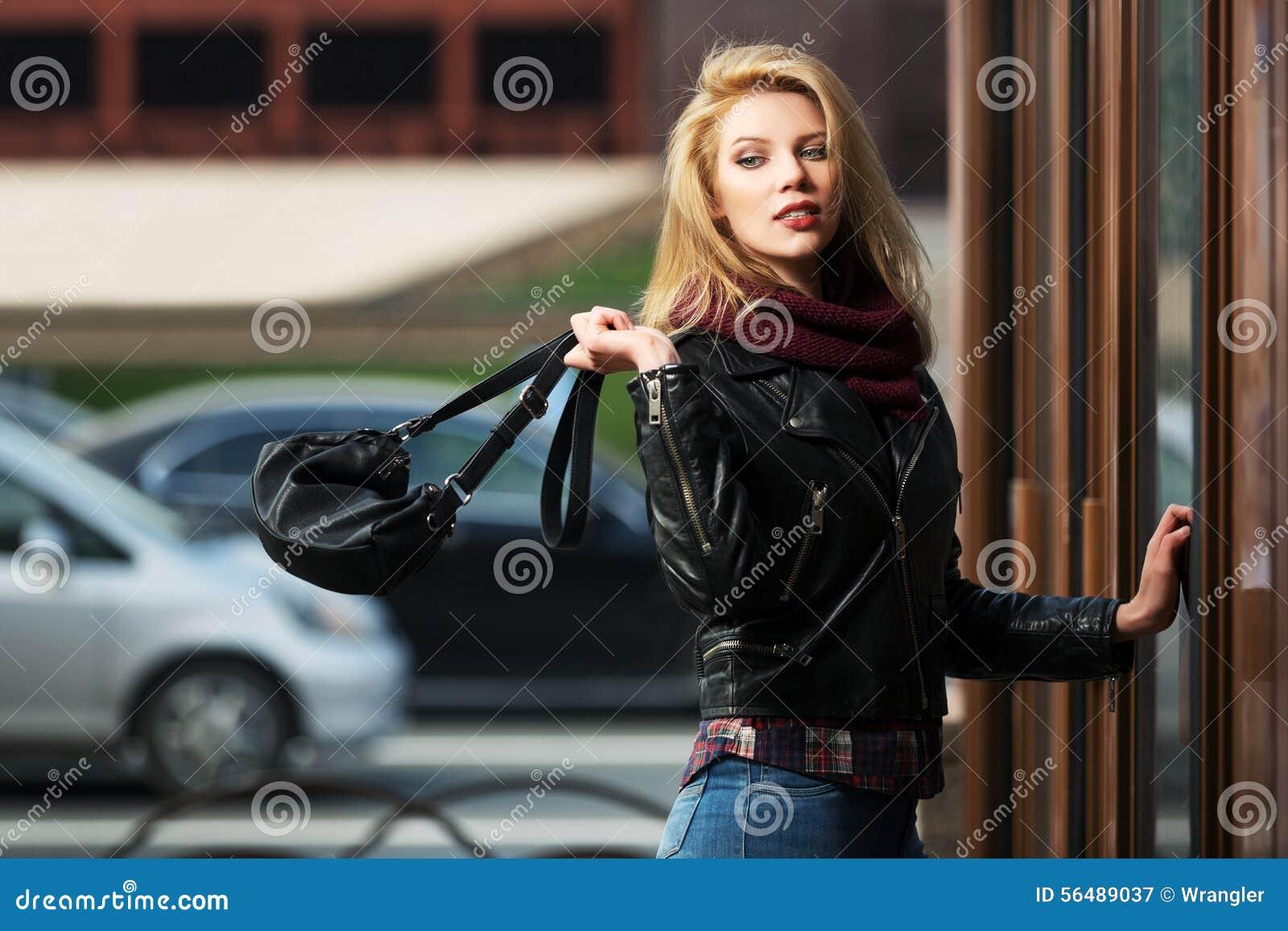 Façonnez la femme blonde avec le sac à main à la porte de mail