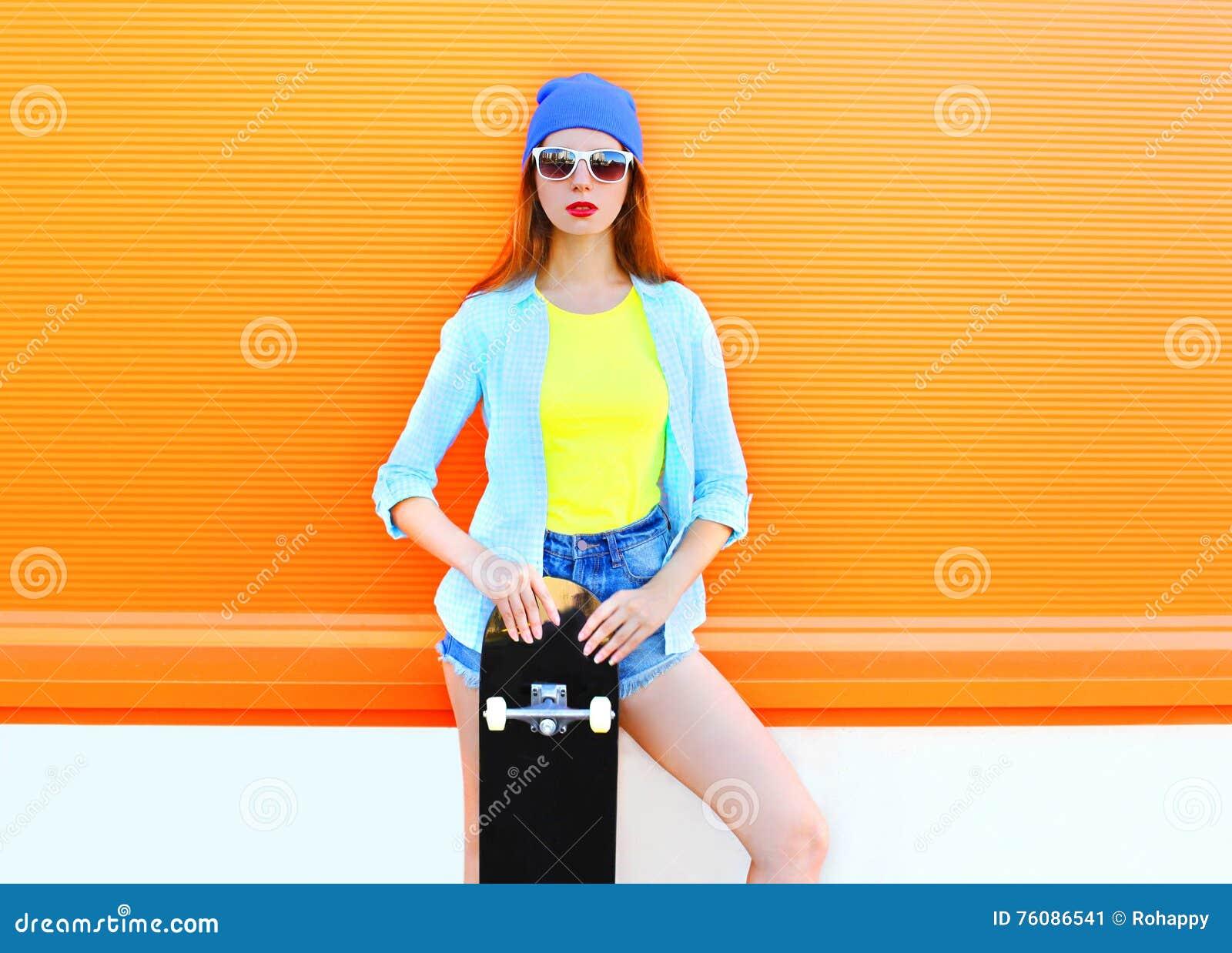 Façonnez la jolie fille avec la planche à roulettes dans la ville au-dessus de l orange colorée