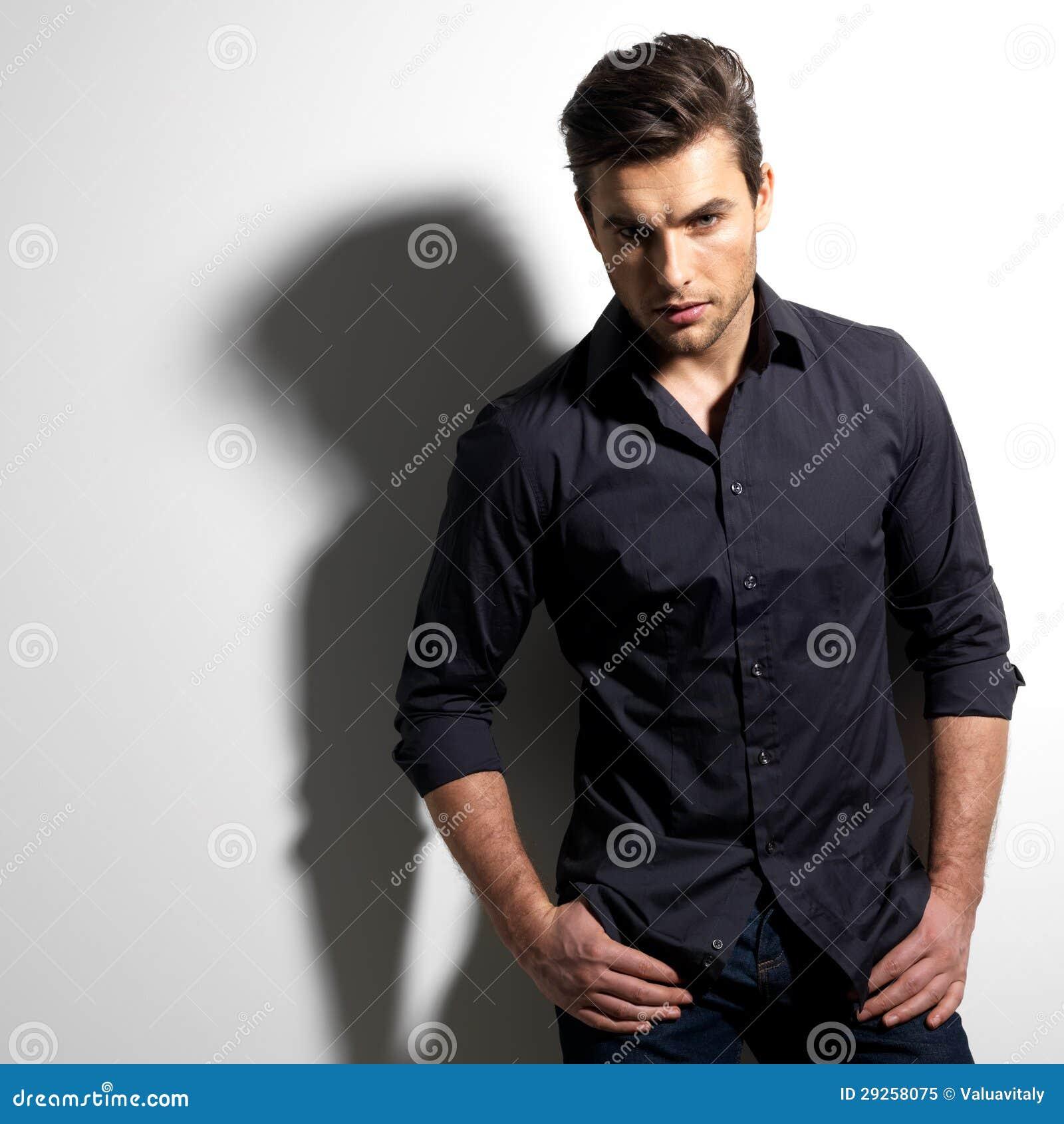 Façonnez la verticale de l jeune homme dans la chemise noire