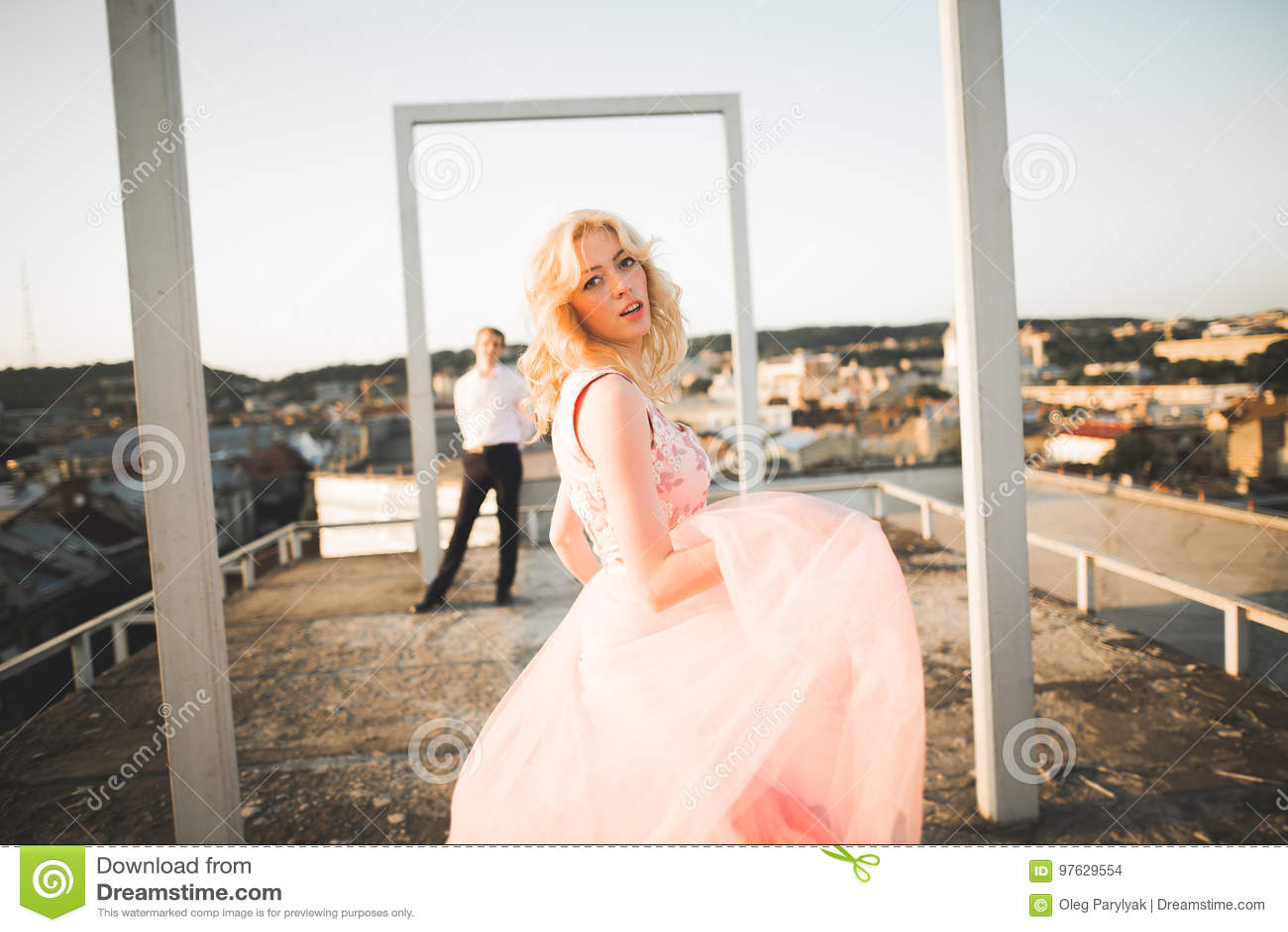 Façonnez les beaux beaux couples posant sur le toit avec le fond de ville Jeune homme et extérieur blond sensuel lifestyle