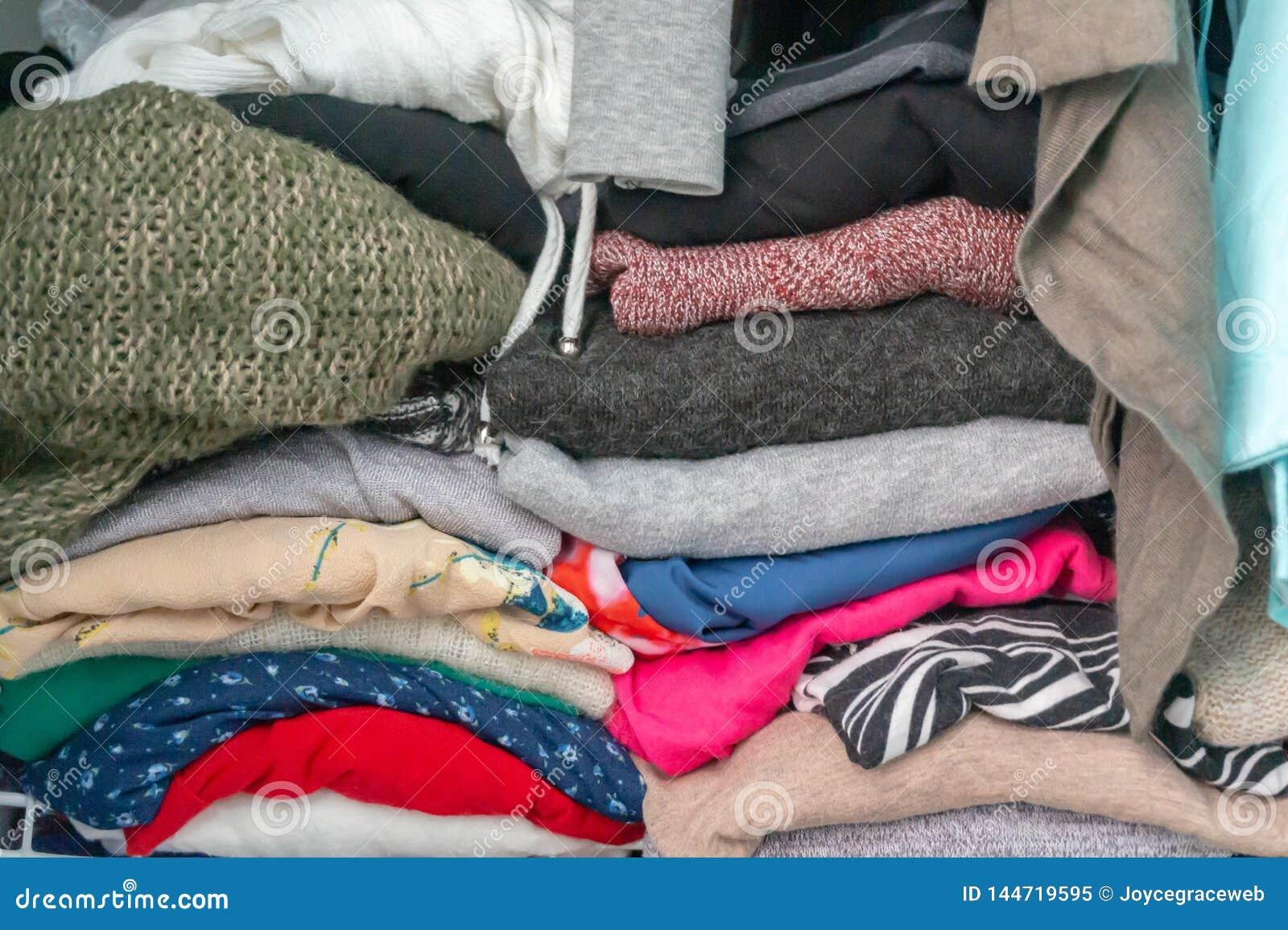 Fałdowi pulowery i szaty kobiety garderoba w szafie Przedstawiać nadmiara potrzeba dla szafy organizacji, tidyin