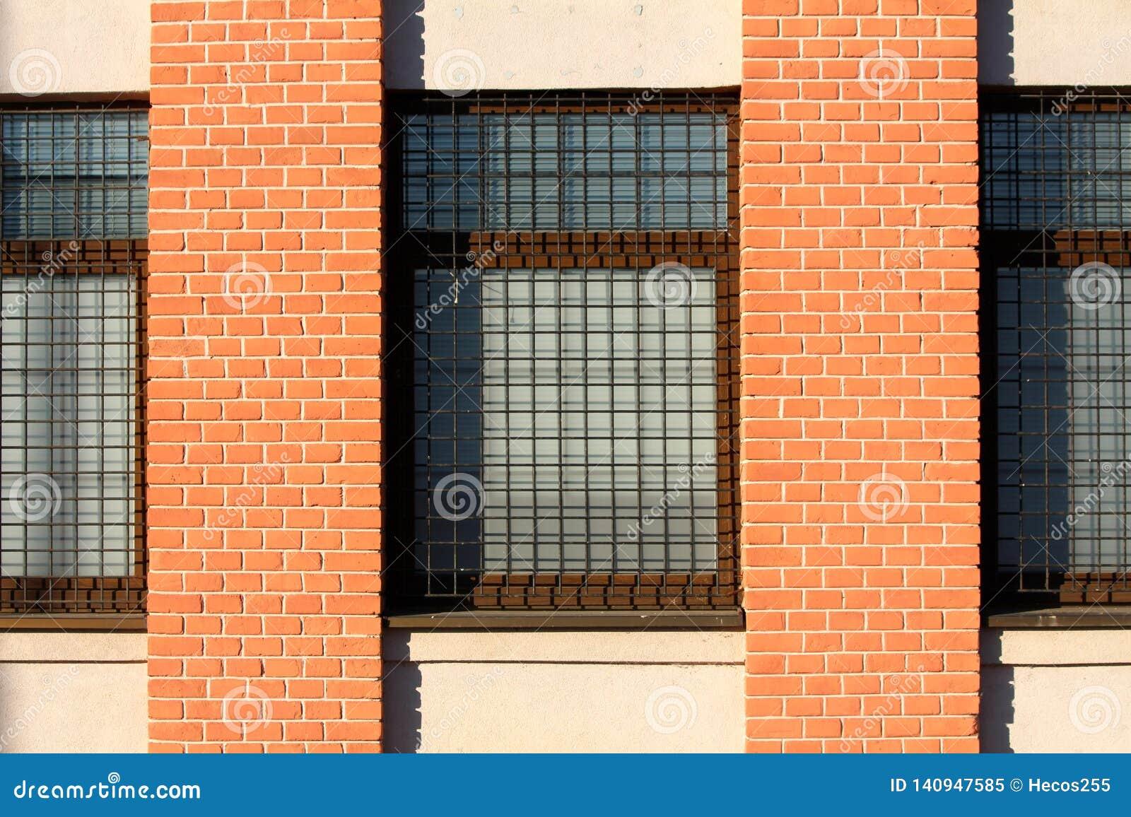 Fabbricato industriale con i pali arancio dei mattoni fra le finestre con protezione arrugginita delle barre di metallo