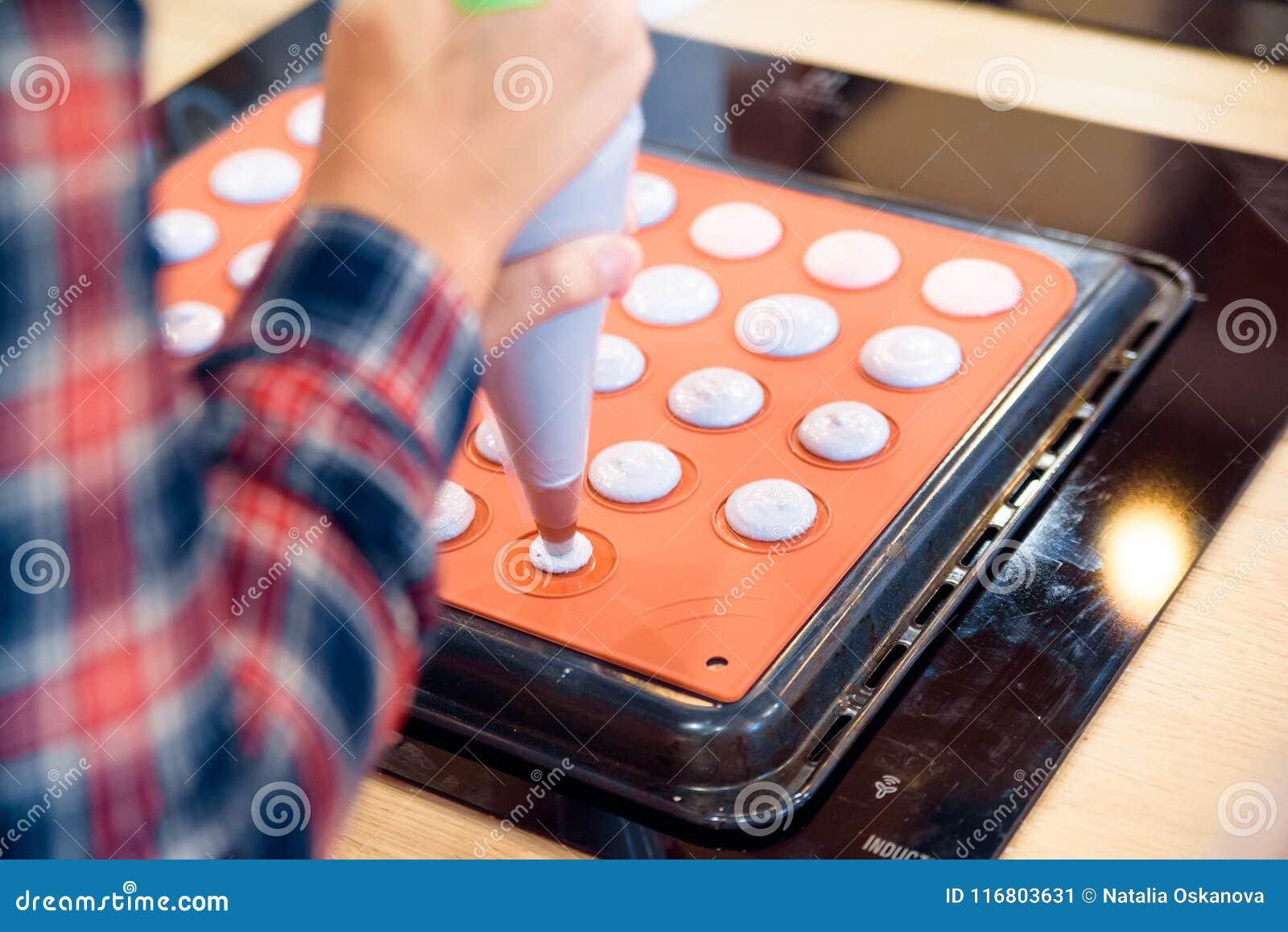Fabbricazione dei macarons con la borsa della pasticceria