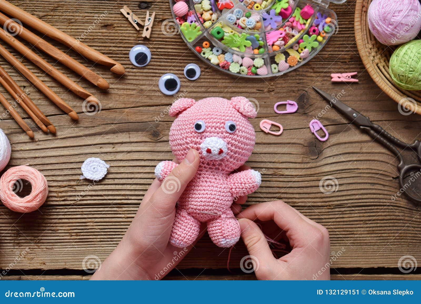 Fabrication du porc rose Faites du crochet le jouet pour l enfant Sur la table filète, des aiguilles, crochet, fils de coton Étap
