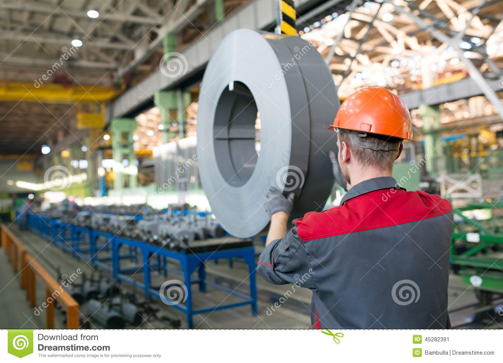 Fabrieksarbeider die lading met kraan vervoeren