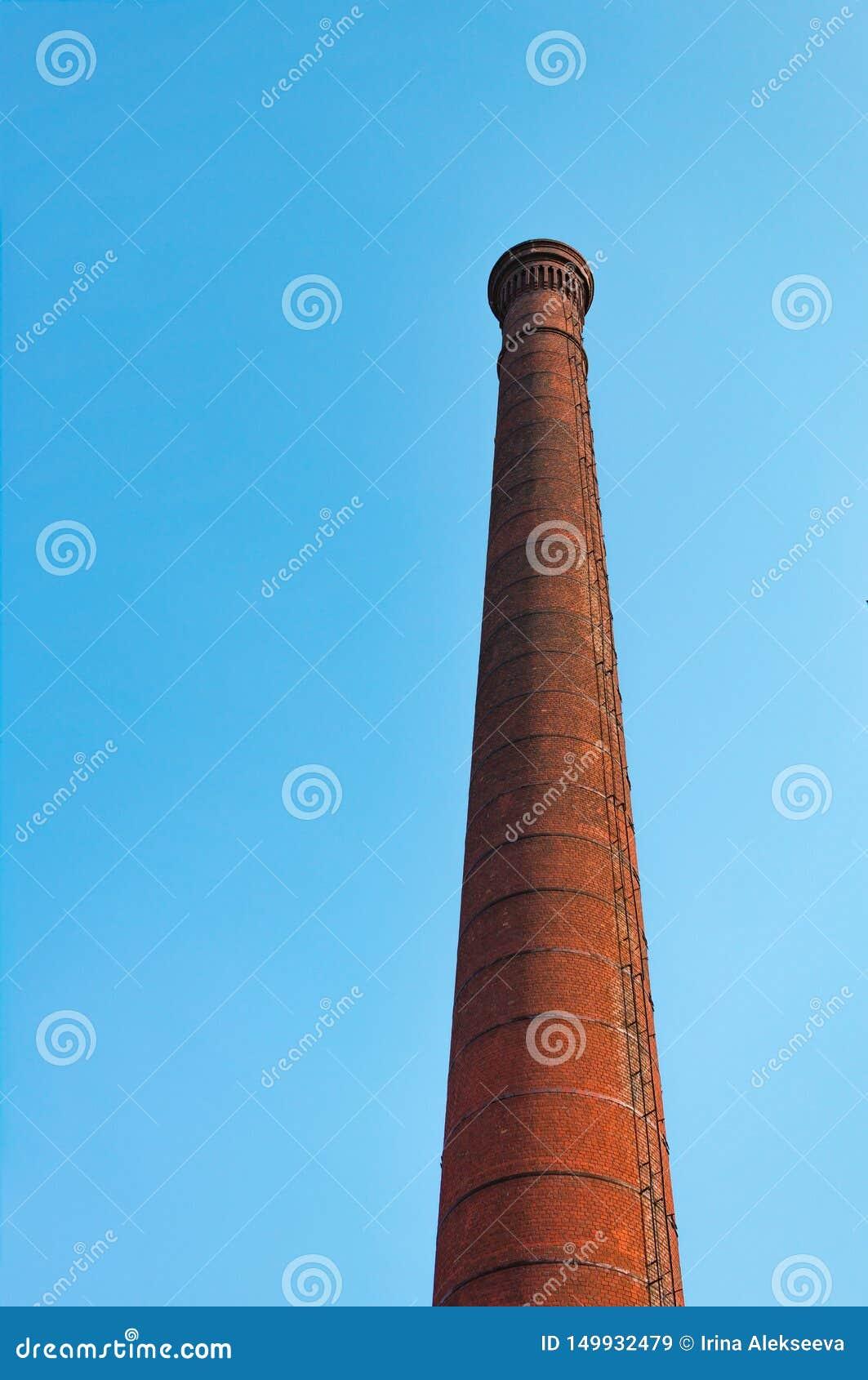 Fabrikrohr des roten Backsteins gegen blauen Himmel Das Konzept der Umweltverschmutzung durch schädliche Emissionen in die Atmosp