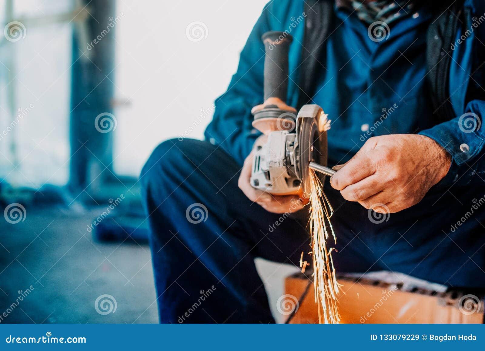 Fabryczny przemysłowego pracownika rozcięcia żelazo i metal używać ostrzarza i wytwarzający iskry na budowie