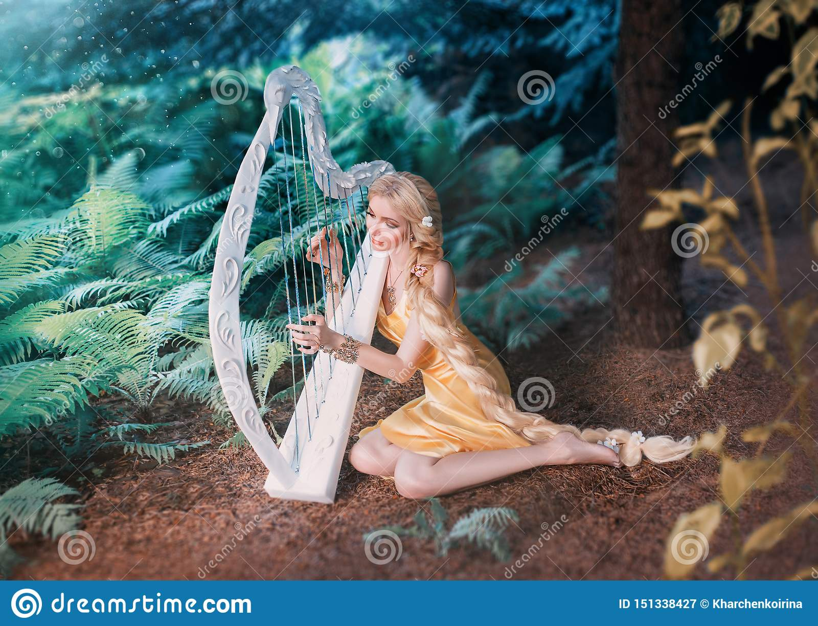 Fabulous forest elf sits under tree and plays on white harp, girl with long blond hair braided in long yellow dress