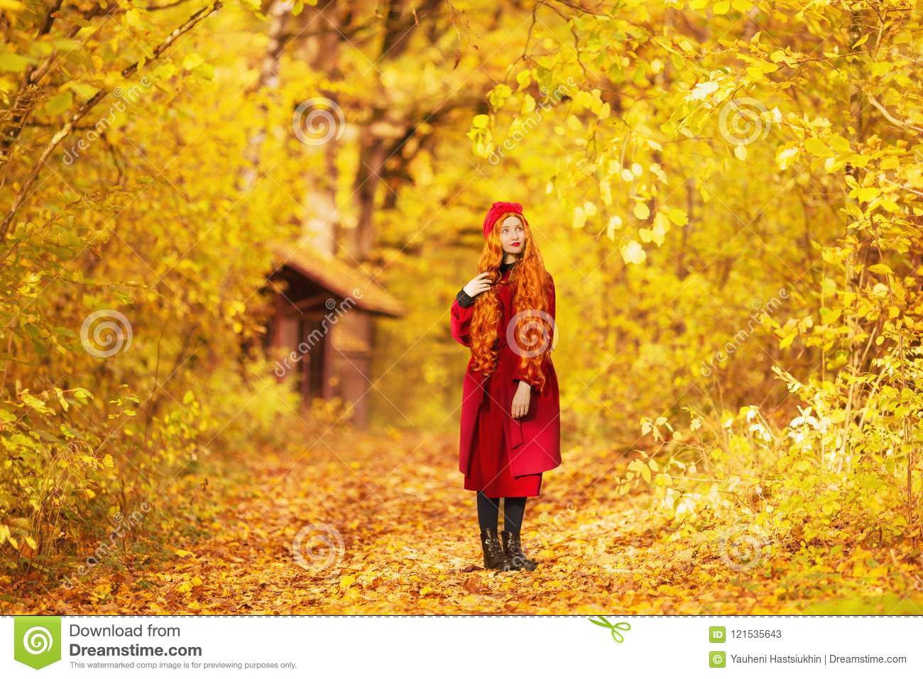 fabulous redhead woman with long curly hair in red coat on autumn background  girl on fabulous
