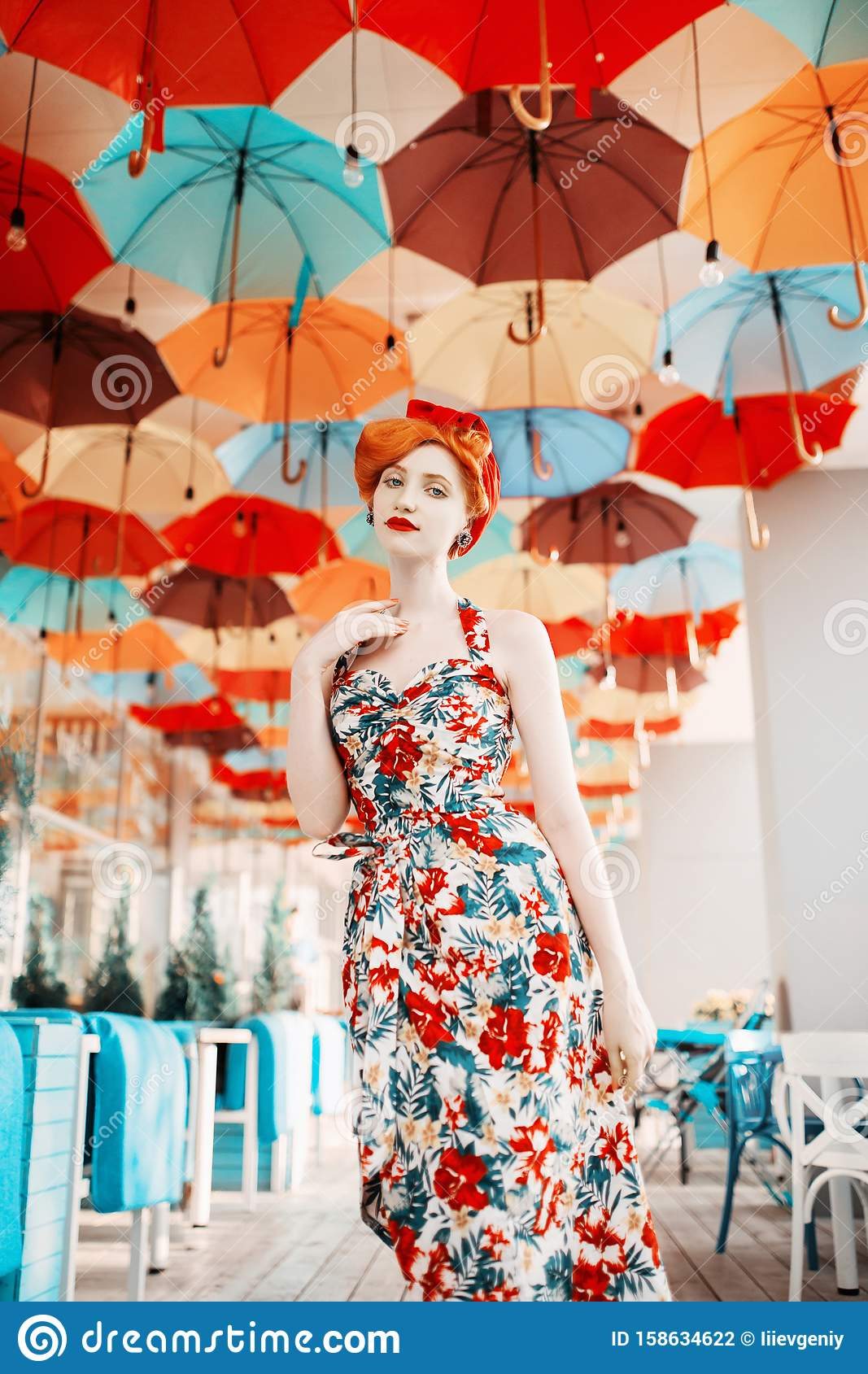 Fabulous retro girl with hairstyle in flower dress on background of colored umbrellas. A beautiful vintage woman with pale skin