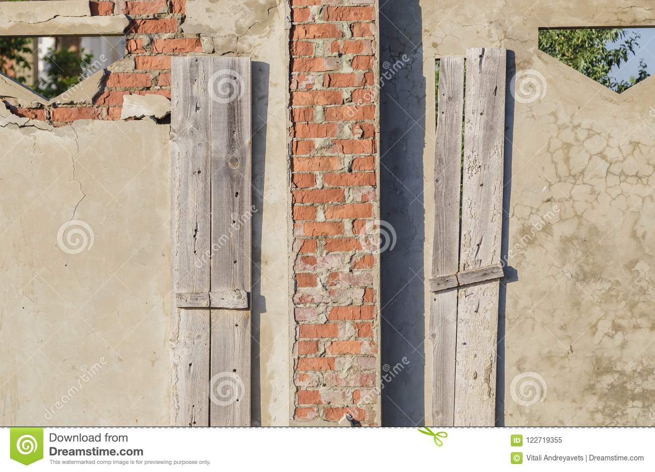 Facade of abandoned building with three doors.