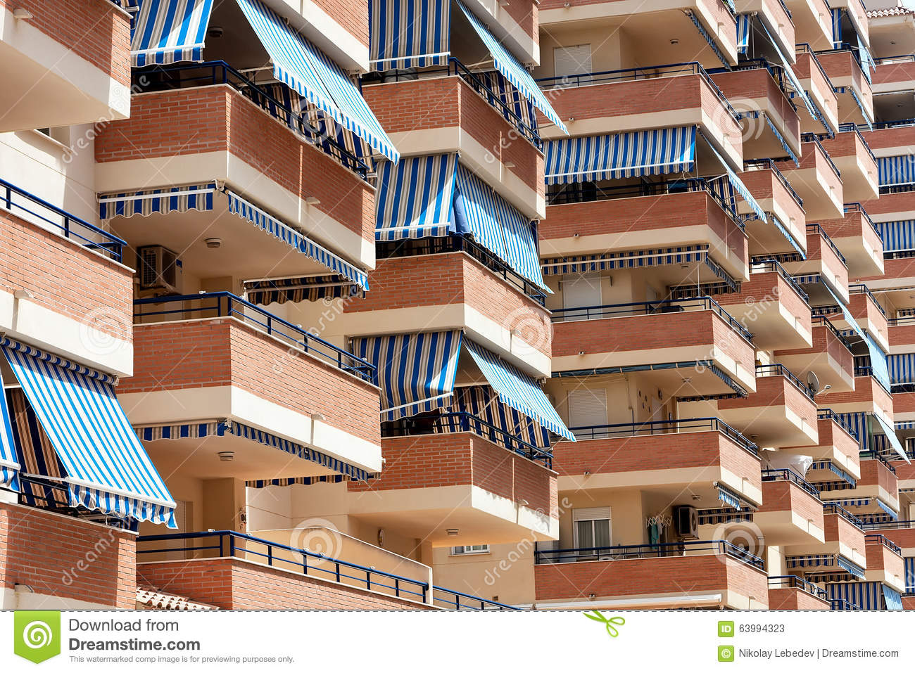 Facade Of Apartment Building With Balconies And Awnings From The