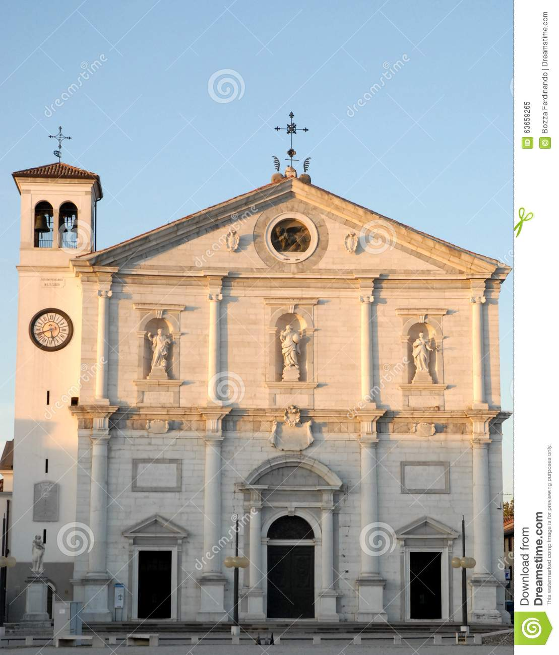 Facade of the church, with three statues, illuminated by the setting sun in Palmanova in Friuli (Italy)