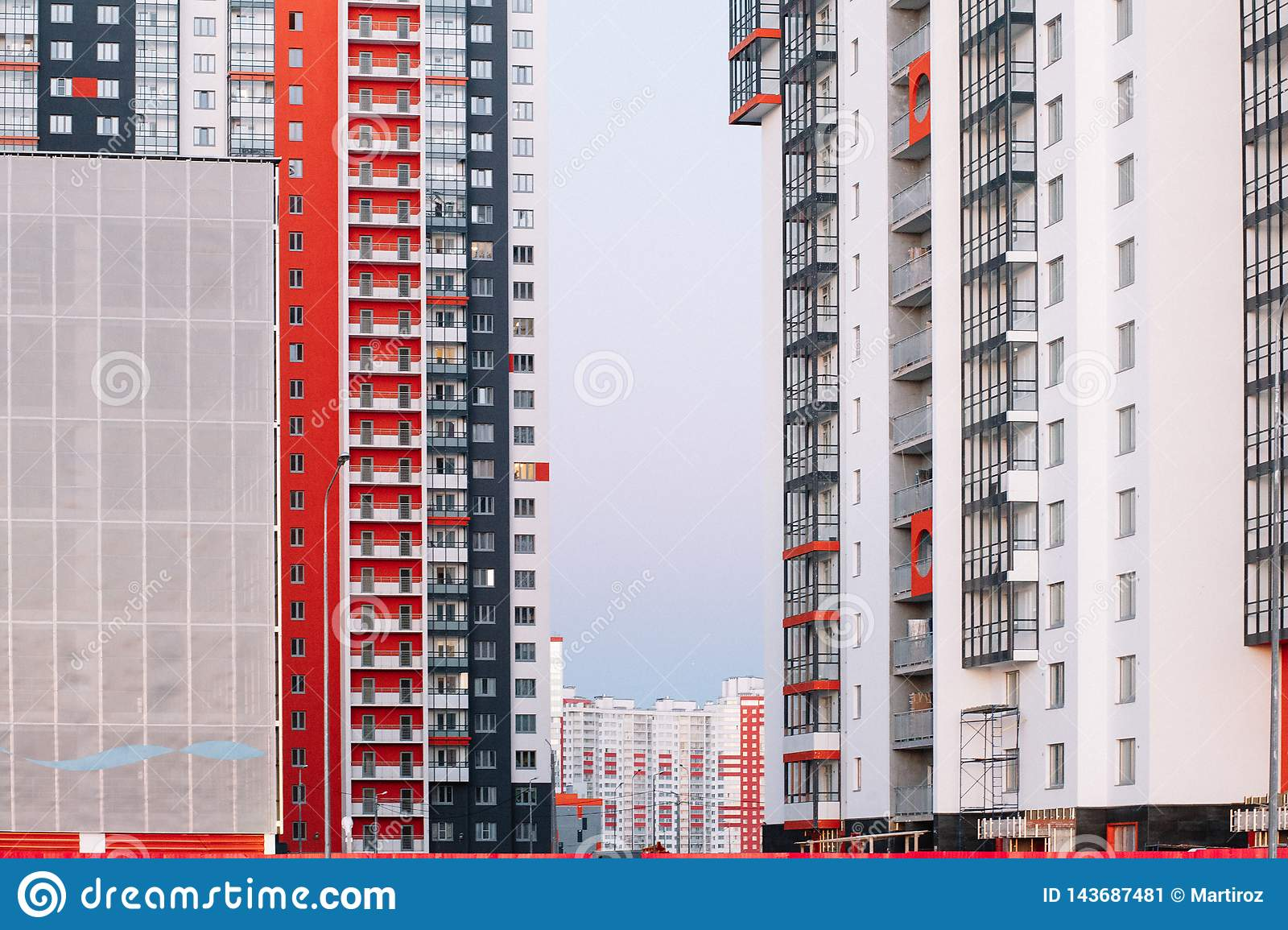 The facade of a high-rise building with red white and gray stripes. Multi-storey building against the blue sky. Background to