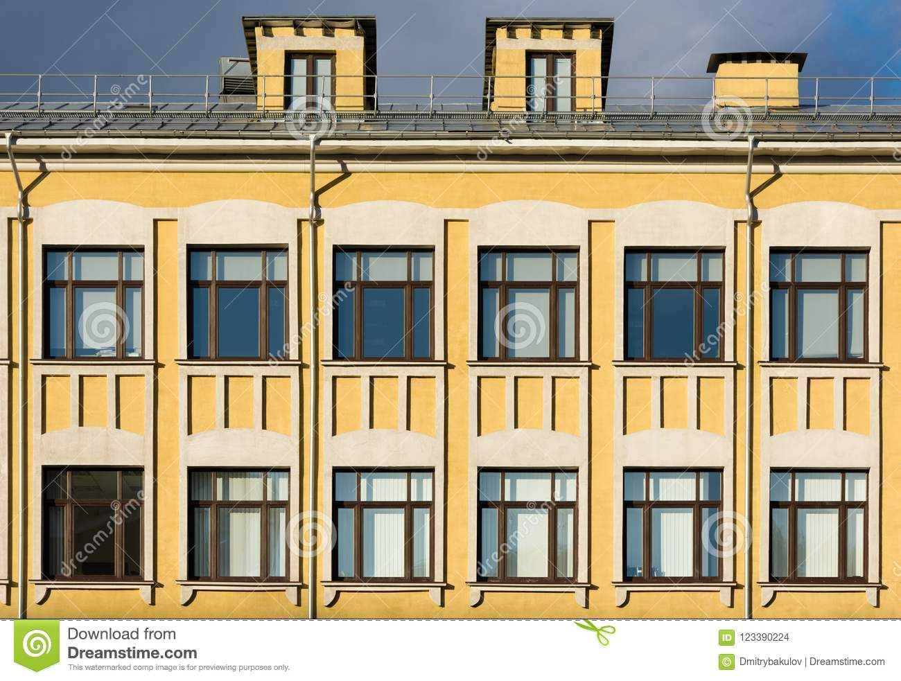 The Facade Of The Old Building With Yellow Walls And White Decor ...